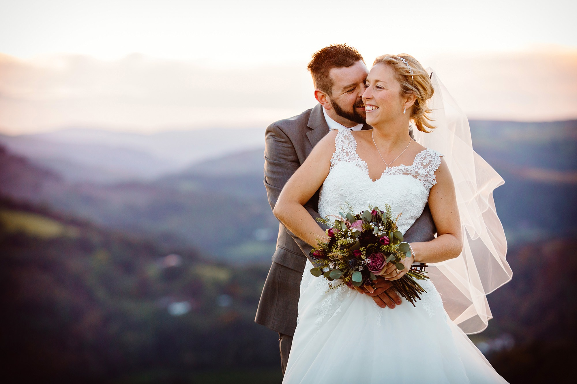 Castell dinas bran wedding photography portrait of groom hugging bride and laughing