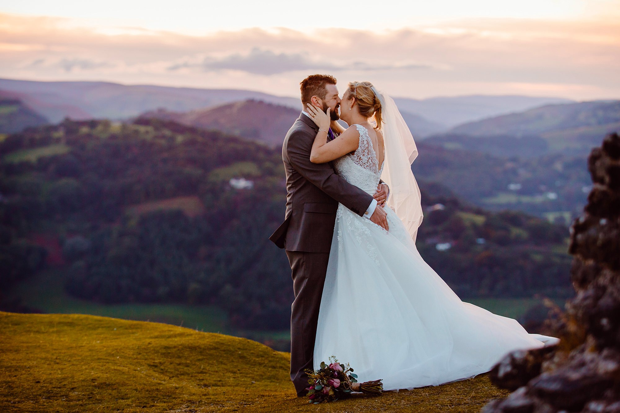 Castell dinas bran wedding photography portrait of a bride kissing her groom at sunset