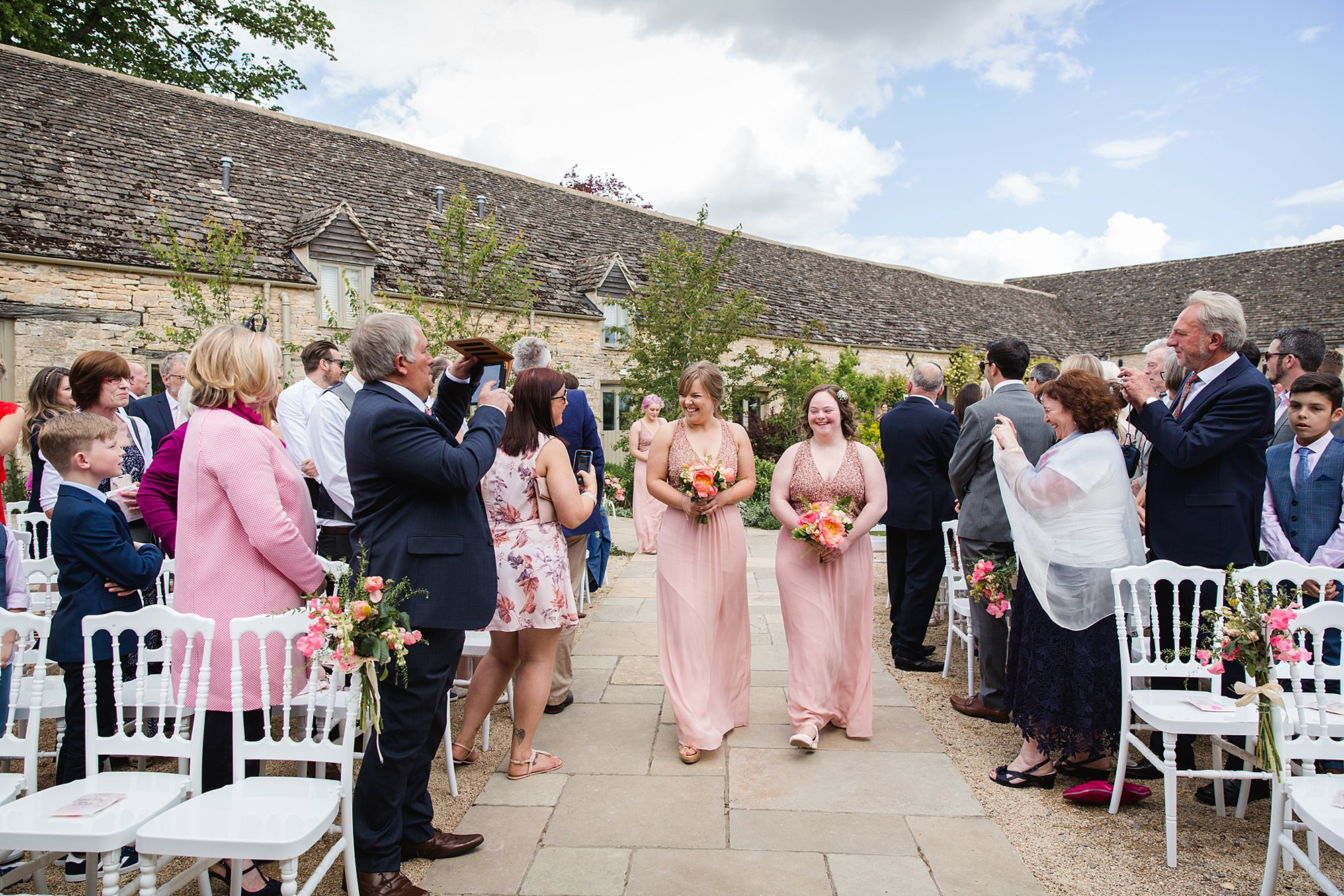 Caswell House Wedding bridesmaids walk down the aisle at outdoor ceremony