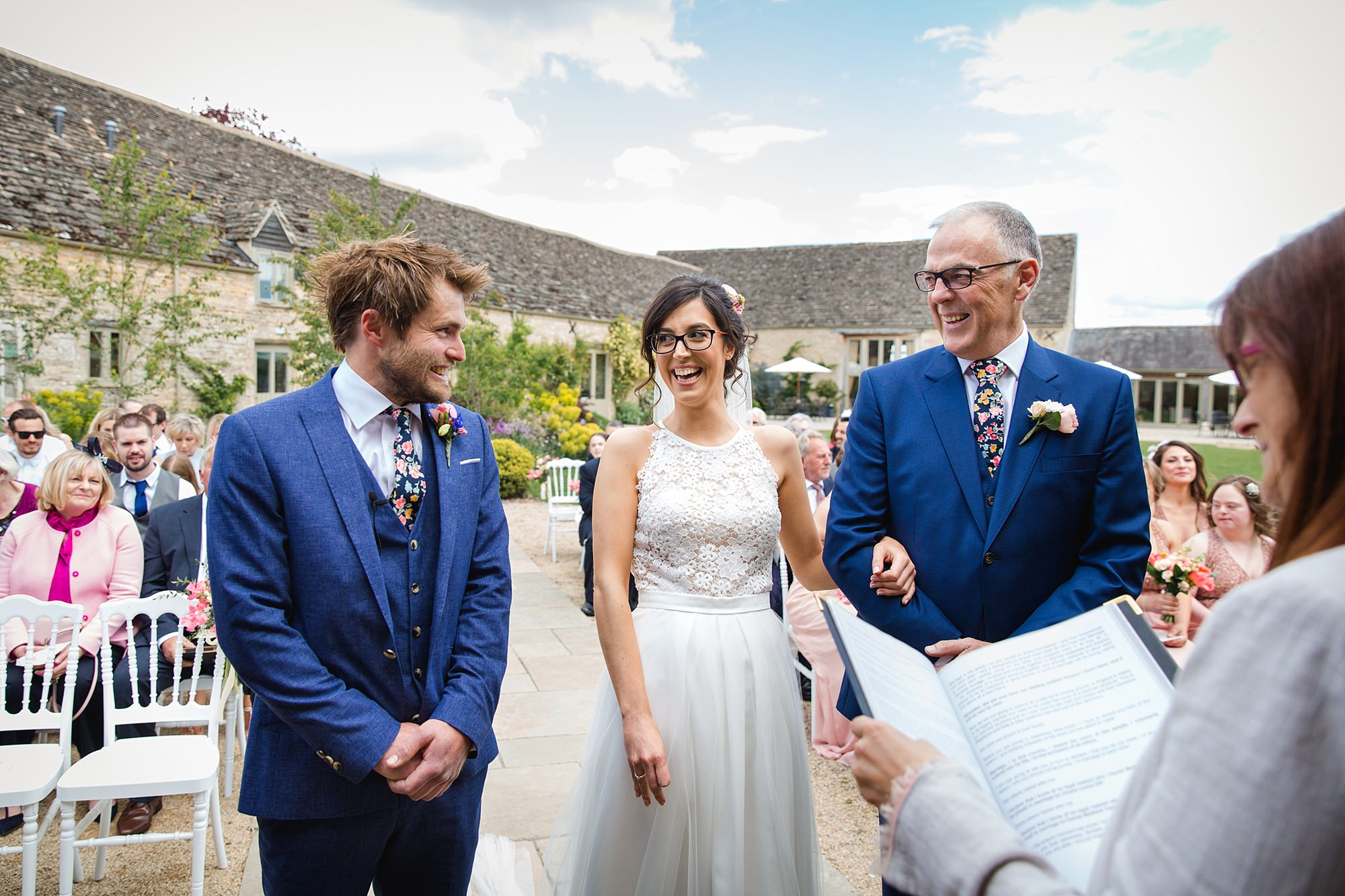 Caswell House Wedding bride laughs with groom and her father during ceremony