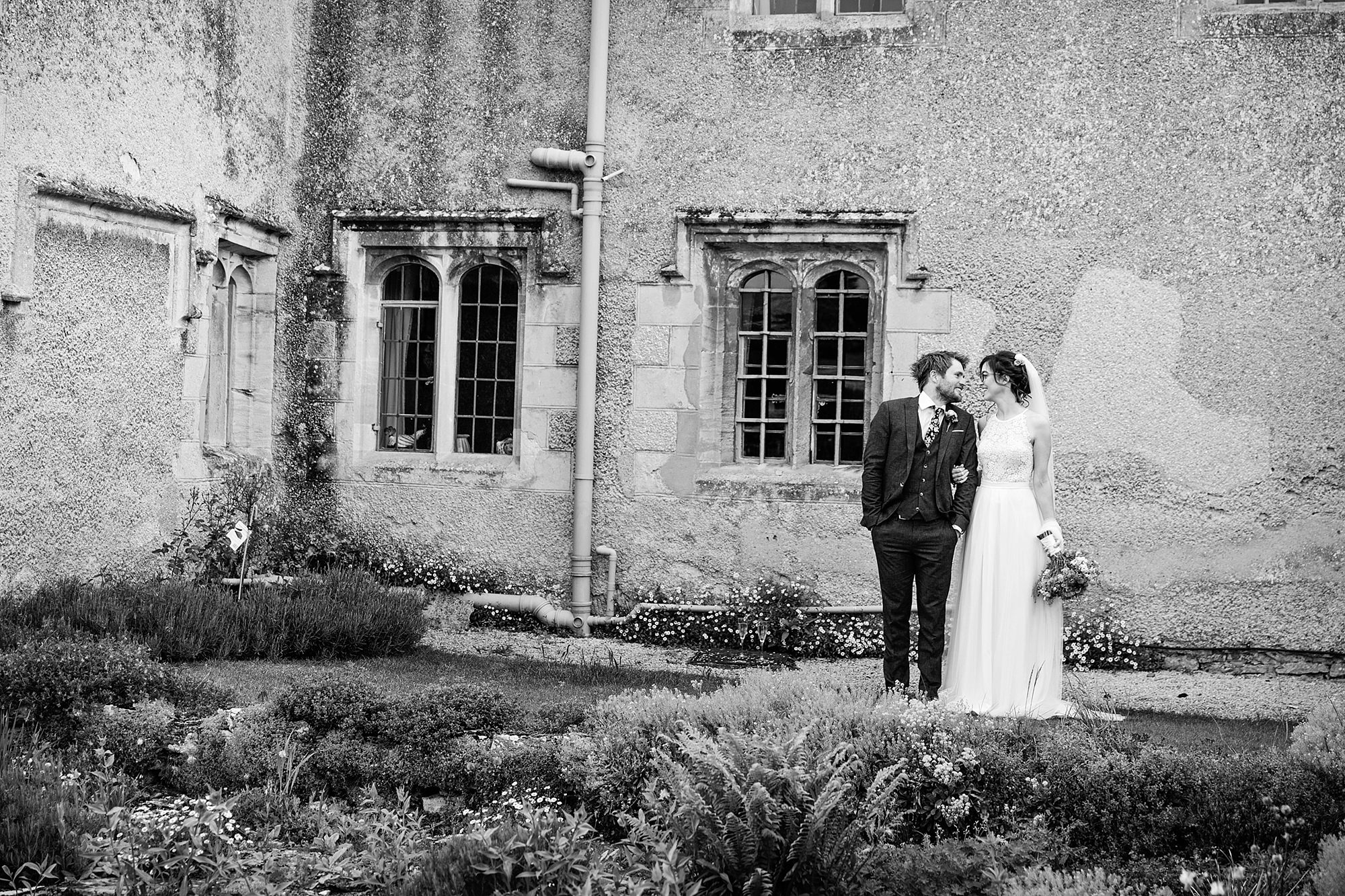 Caswell House Wedding a bride and groom stand together in gardens