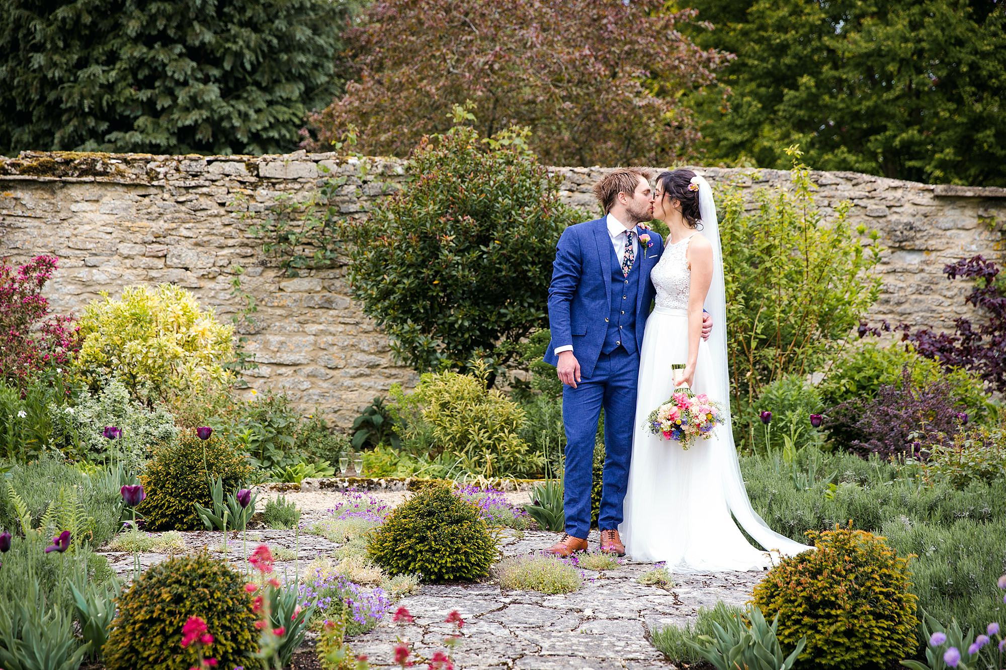 Caswell House Wedding bride and groom kiss in gardens
