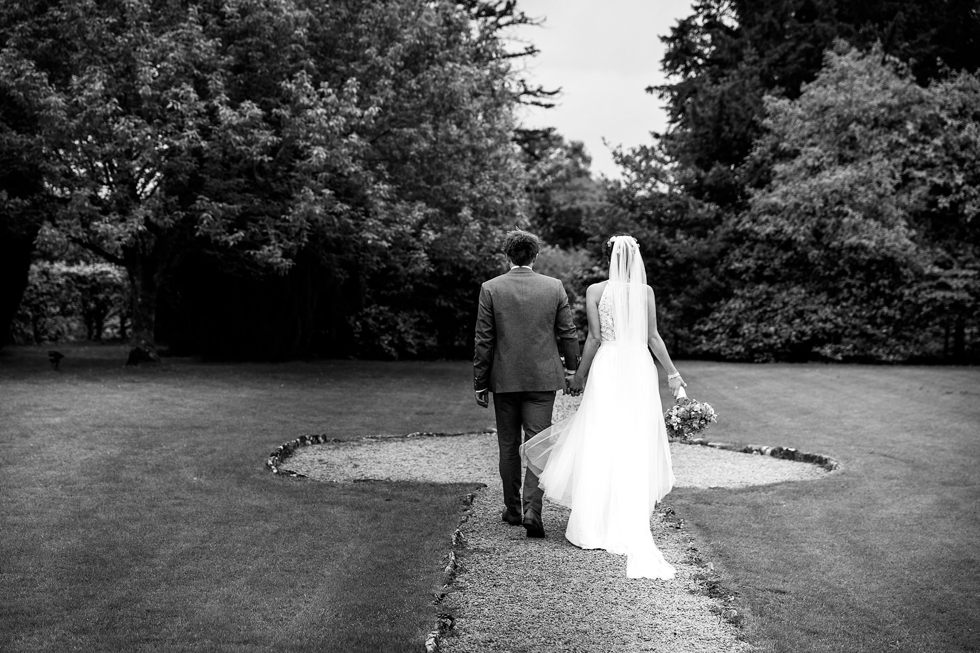 Caswell House Wedding bride and groom walk through the gardens