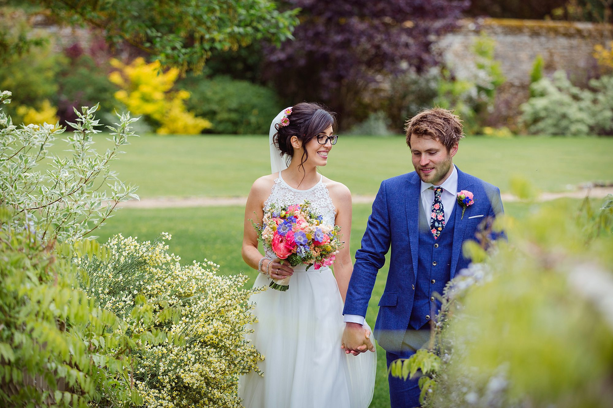 Caswell House Wedding groom and bride walk and laugh together in gardens