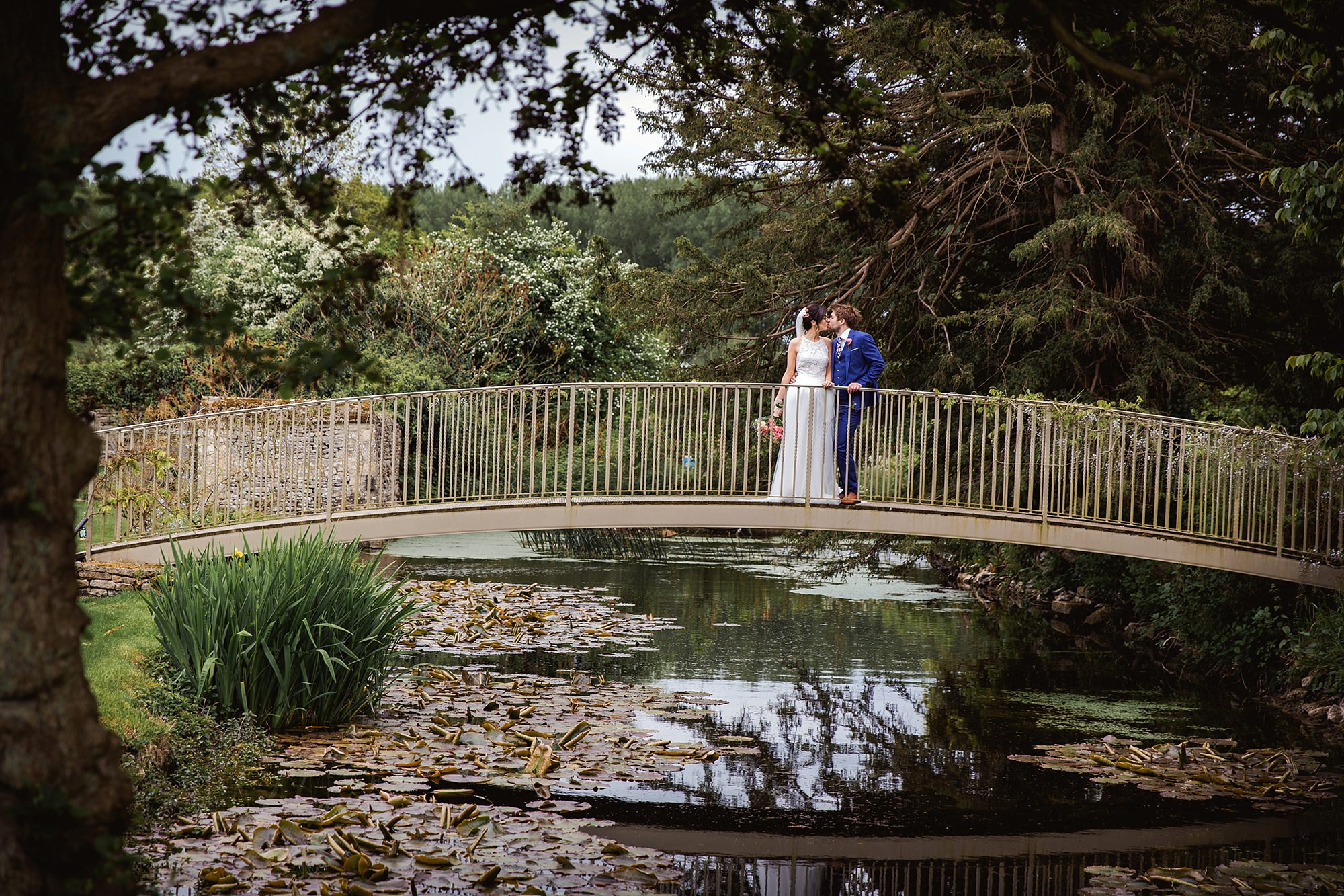 Caswell House Wedding portrait of bride and groom kissing on a bridge over the pond
