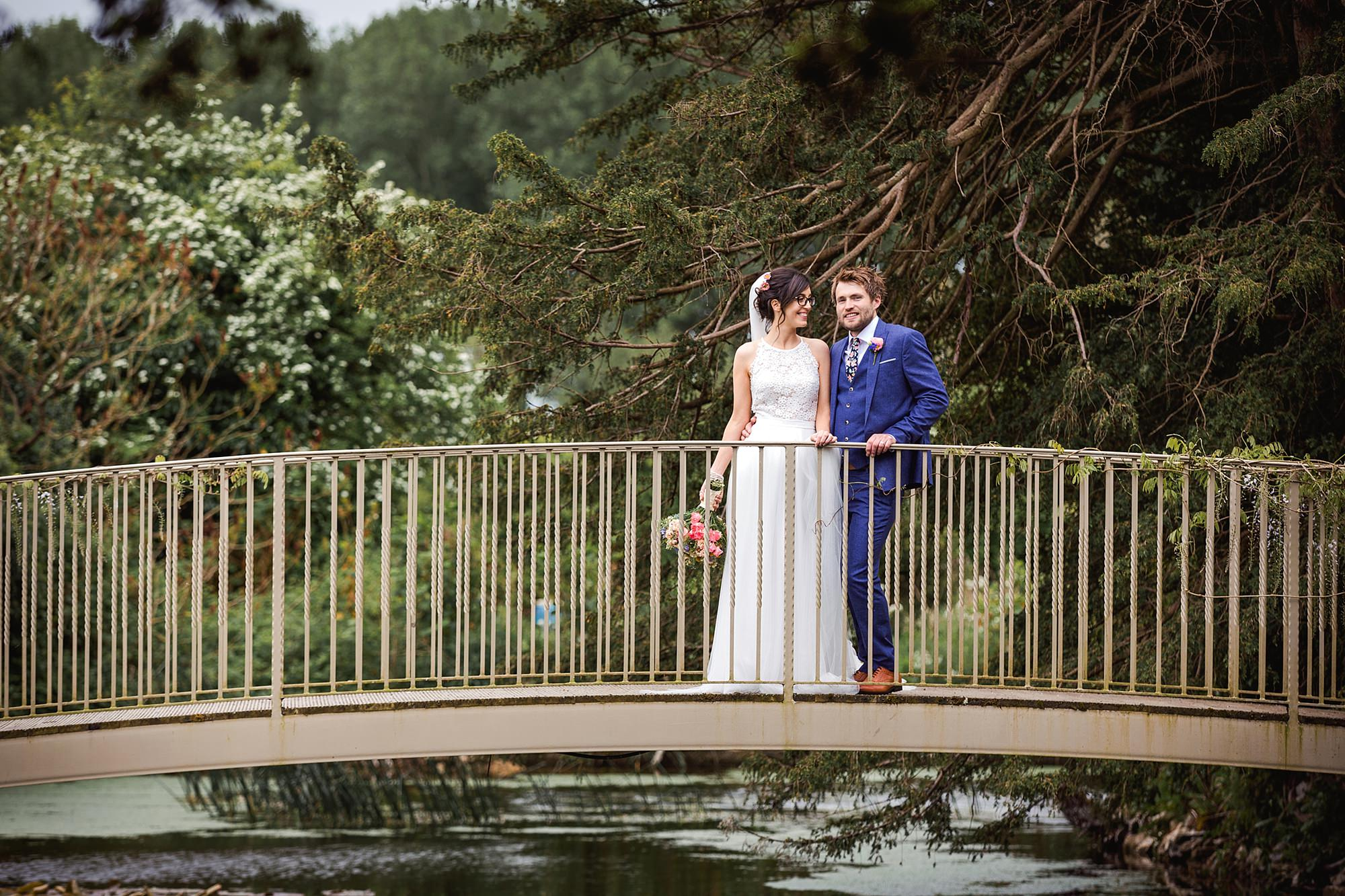 Caswell House Wedding close up portrait of bride and groom stood on a bridge