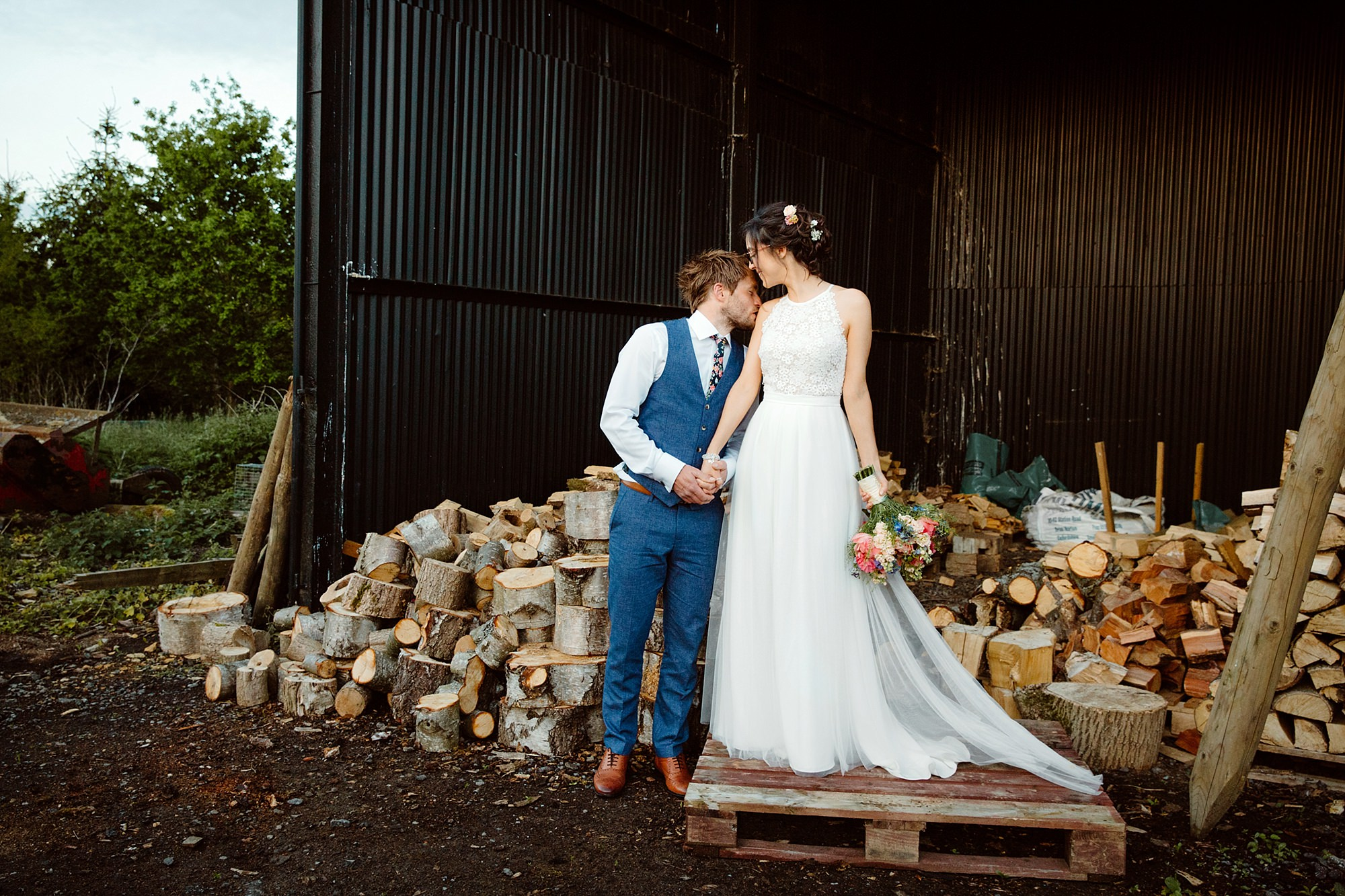 Caswell House Wedding portrait of groom kissing his bride on top off log pile