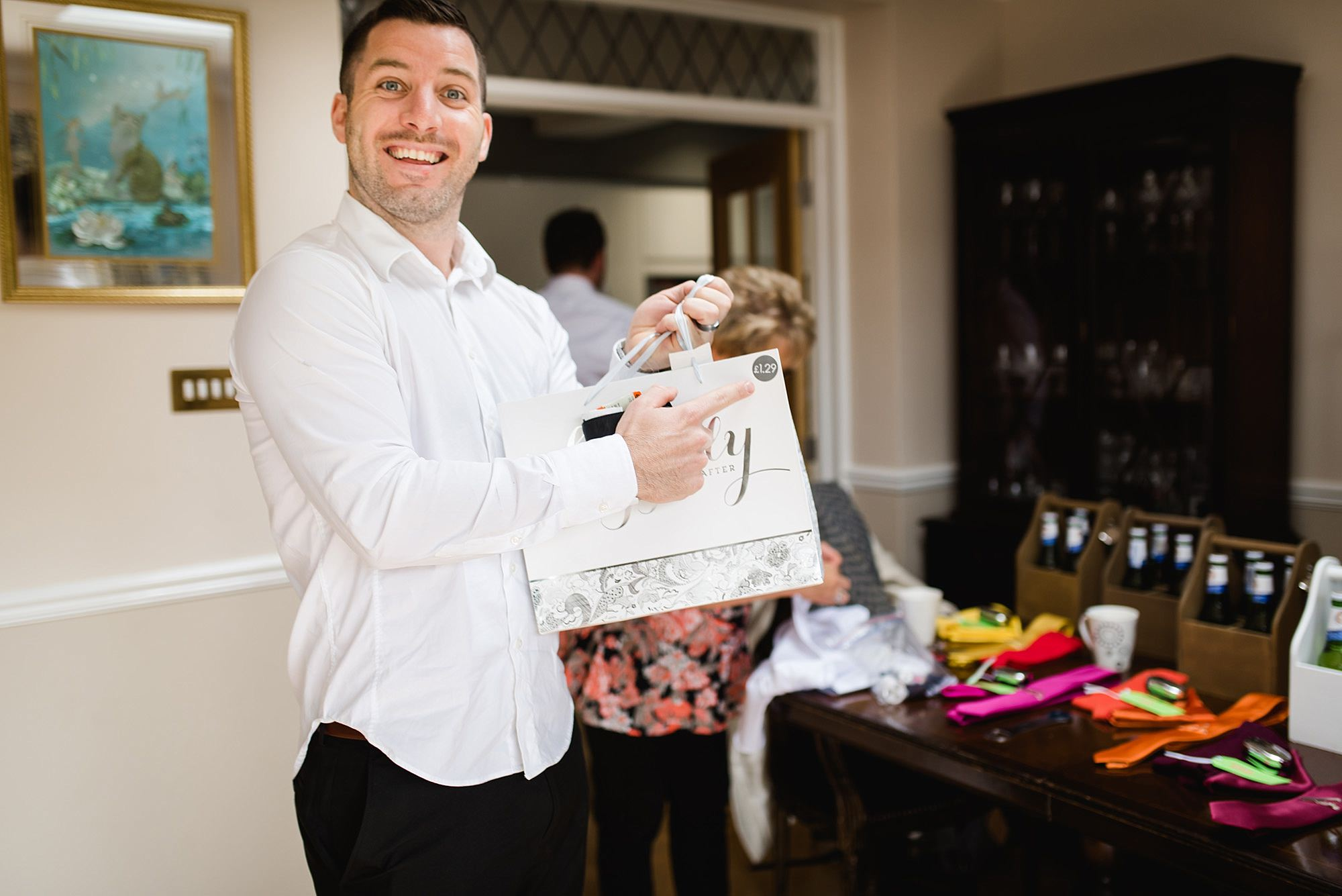 Fun London Wedding funny picture of groomsman showing off price sticker on gift bag