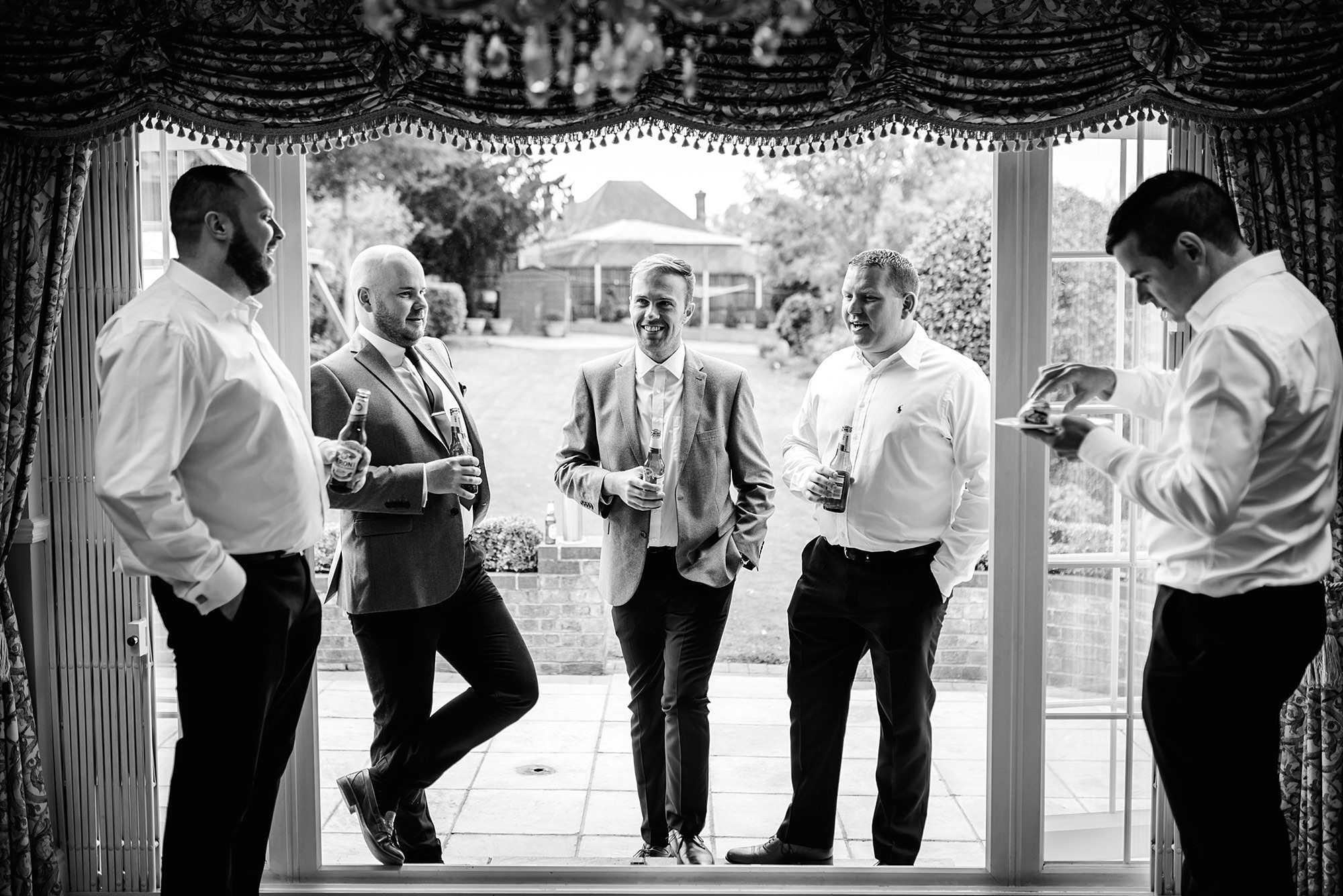 Fun London Wedding groomsmen chat together while getting ready ahead of brixton wedding