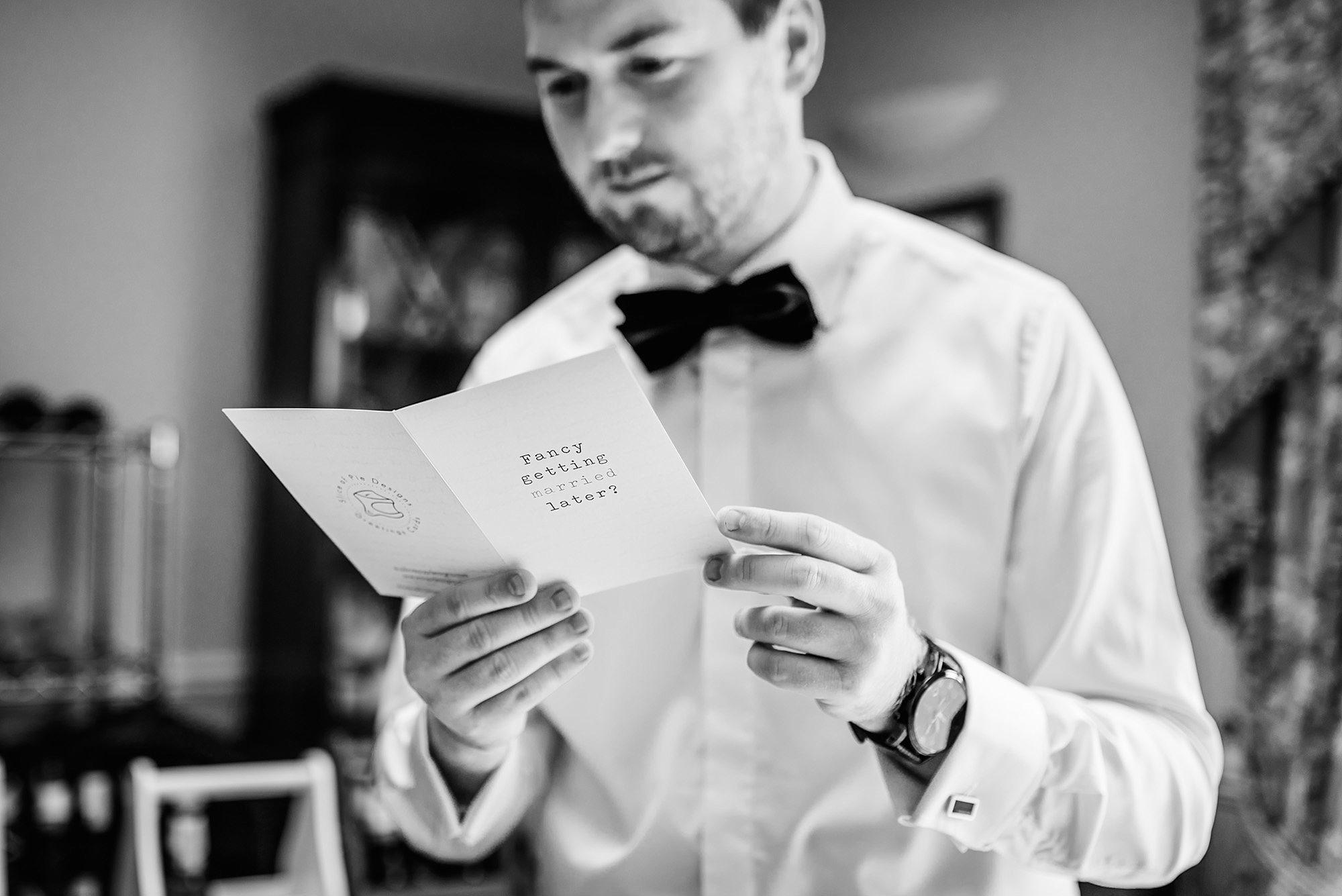 Fun London Wedding groom reads a card from bride