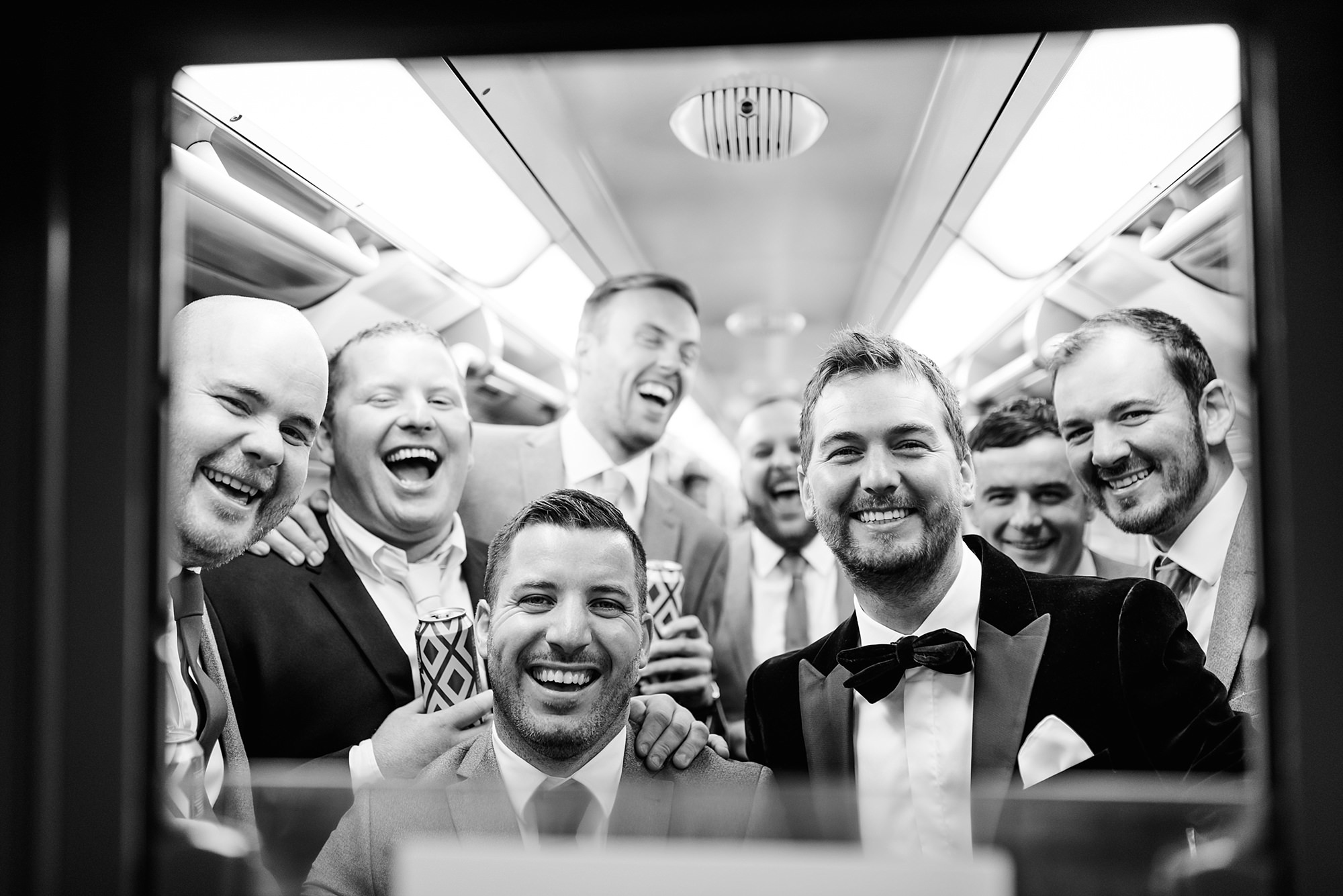 Fun London Wedding funny portrait of from and groomsmen through tube window