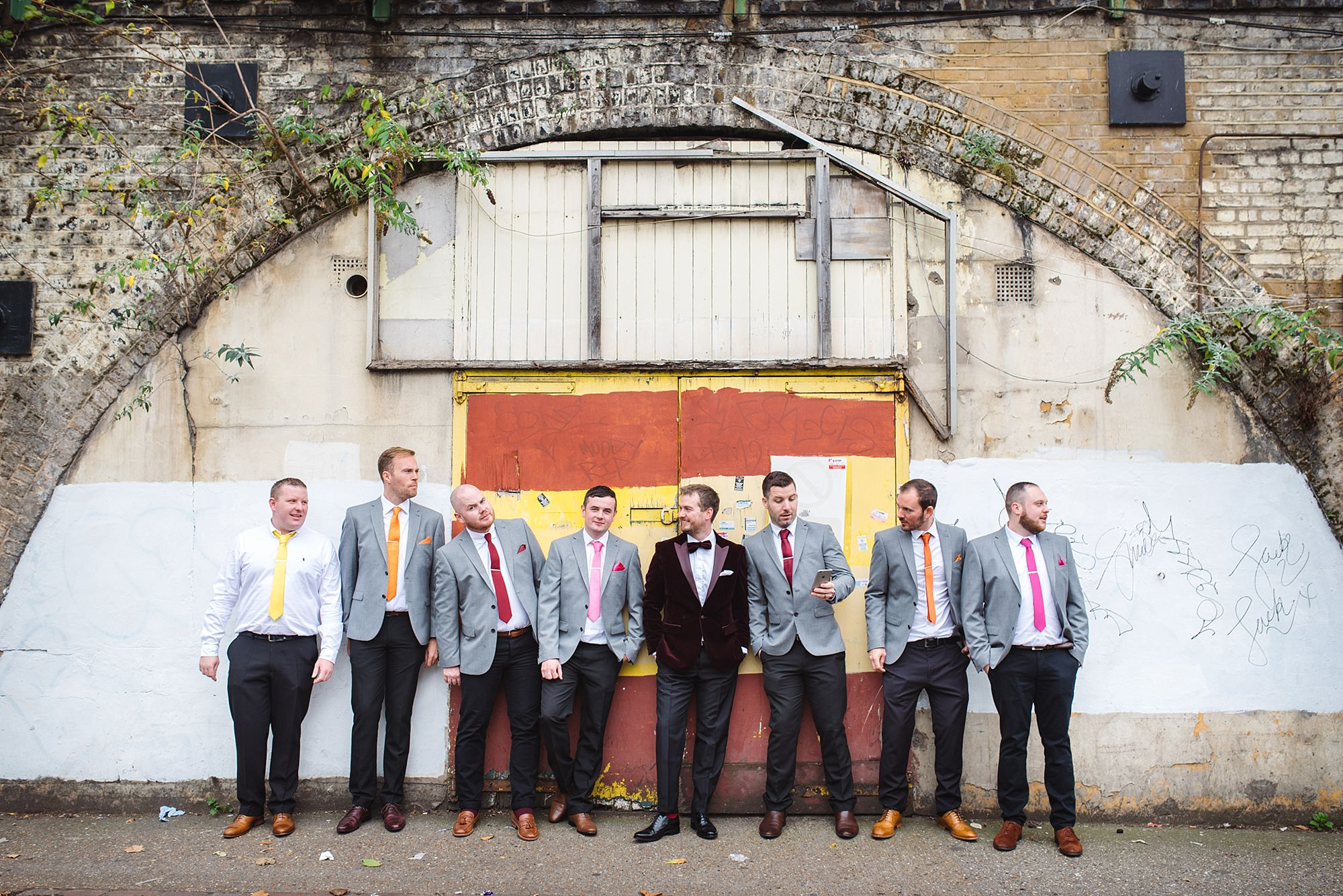 Fun London Wedding groom and groomsmen together in front of a shop in brixton