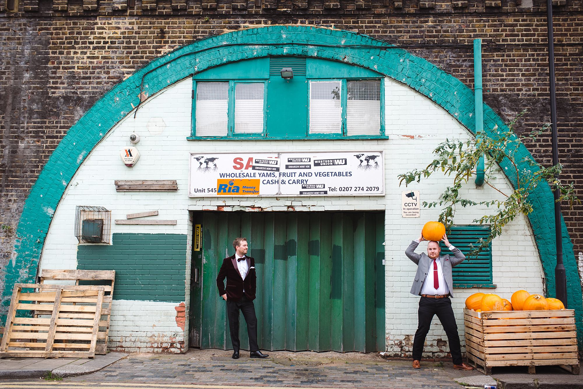 Fun London Wedding groom and groomsman pose with a pumpkin in front of grocery shop in brixton