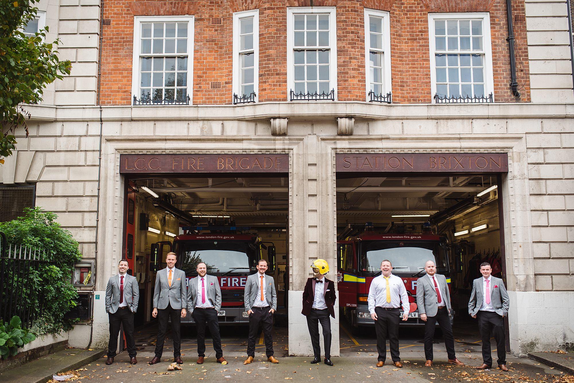Fun London Wedding groom wearing fireman's helmet with groomsmen in front of brixton fire station