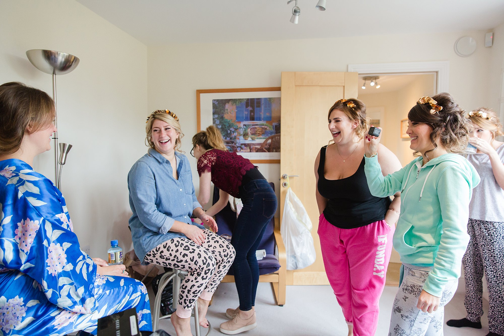 Fun London Wedding bridesmaids laugh with the bride and she gets ready