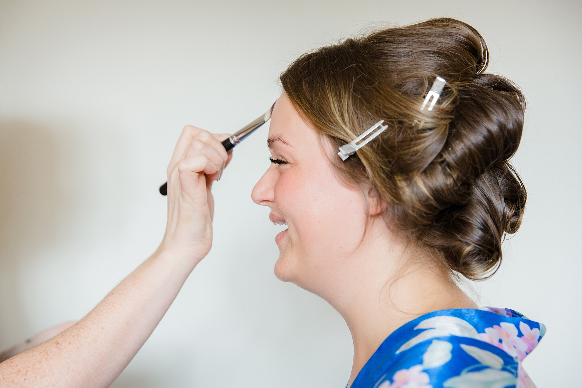 Fun London Wedding portrait of bride laughing as she has her makeup applied