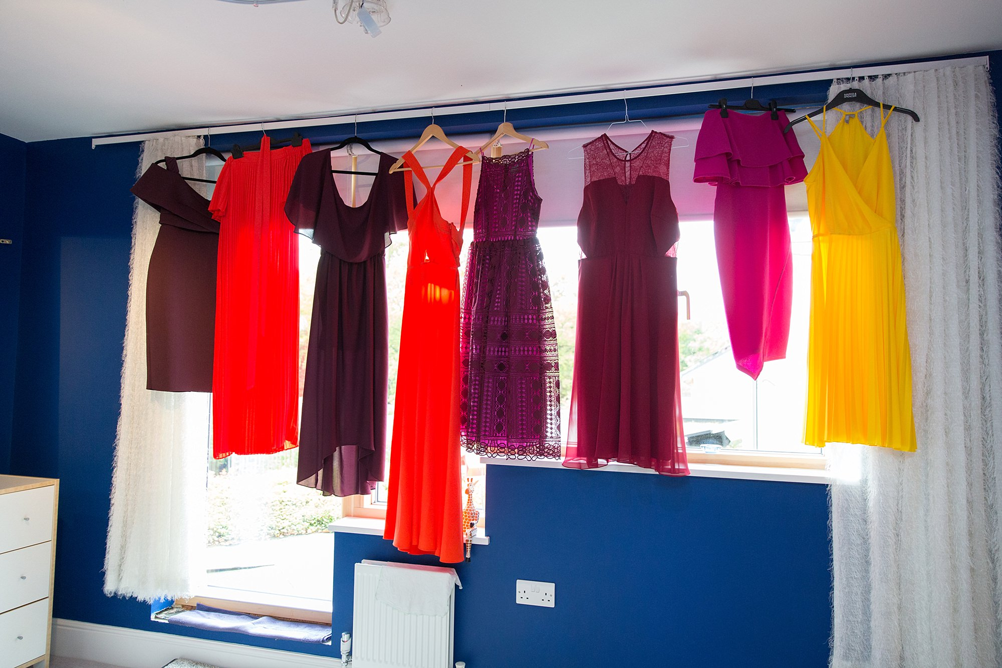 Fun London Wedding colourful bridesmaids dresses hung up in a row