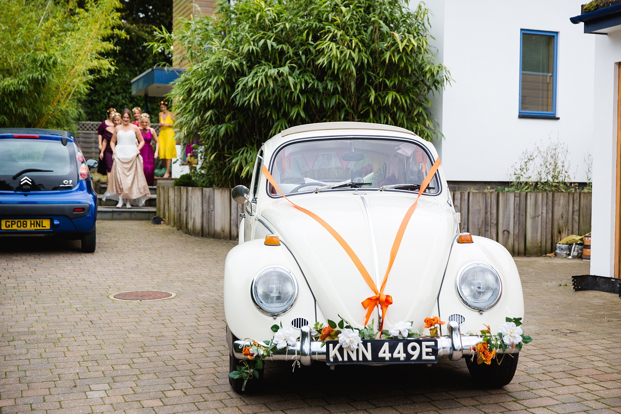 Fun London Wedding bride and bridesmaids walk towards vintage wedding VW beetle