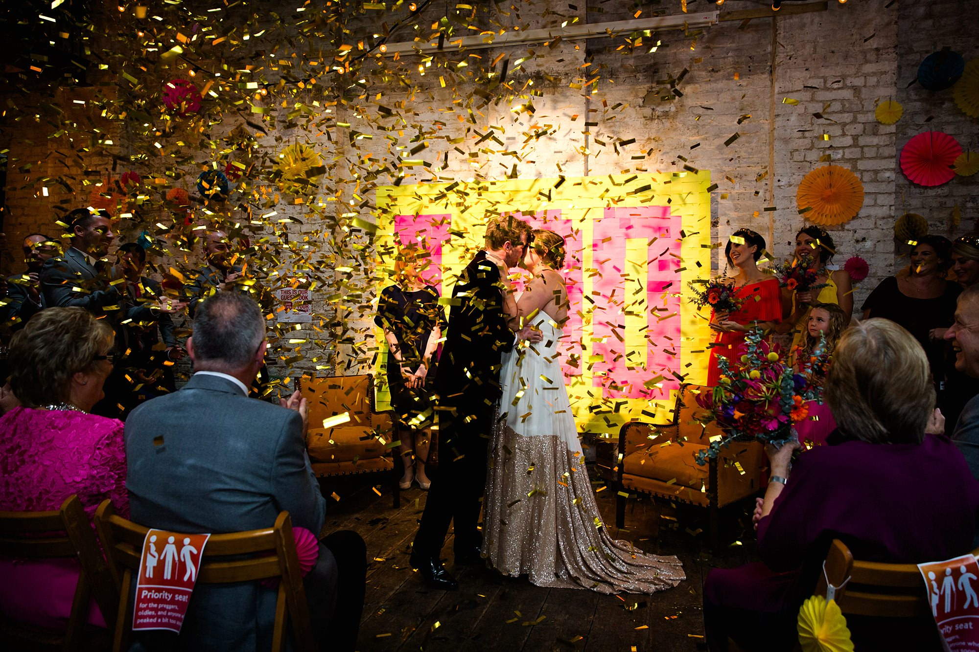 Fun London Wedding bride and groom kiss under confetti cannons