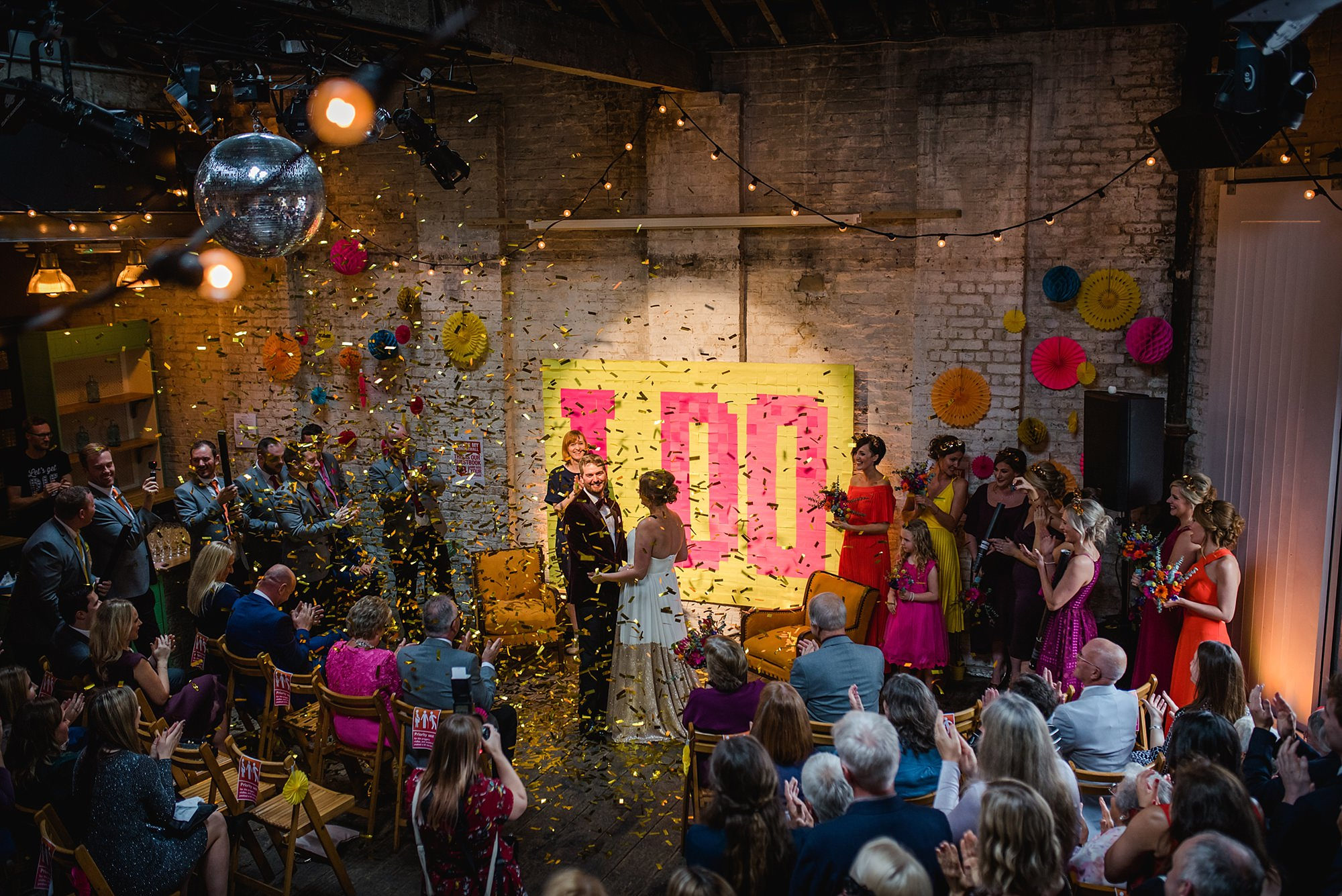 Fun London Wedding portrait of bride and groom in brixton ceremony room with confetti cannons