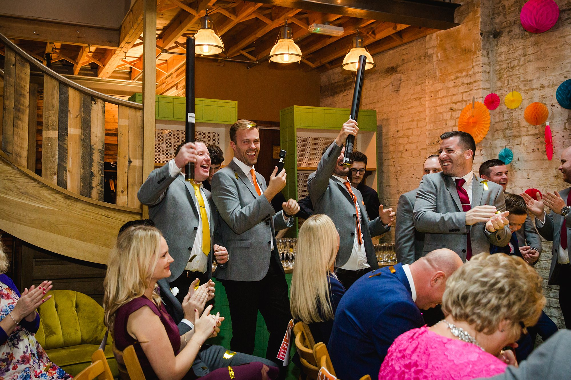 Fun London Wedding groomsmen cheering with confetti cannons