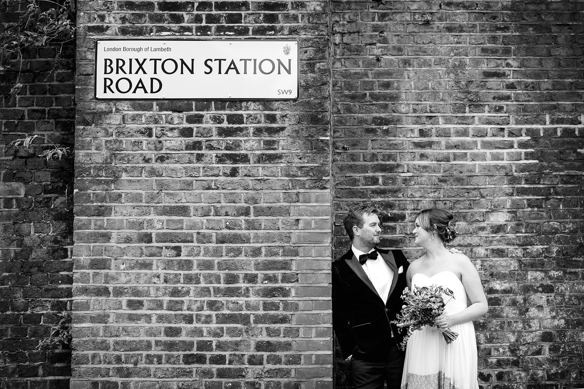 Fun London Wedding portrait of bride and groom next to brixton station road sign
