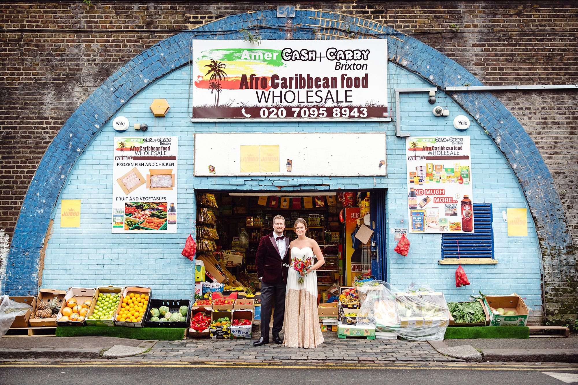 Fun London Wedding portrait of bride and groom outside brixton grocers shop