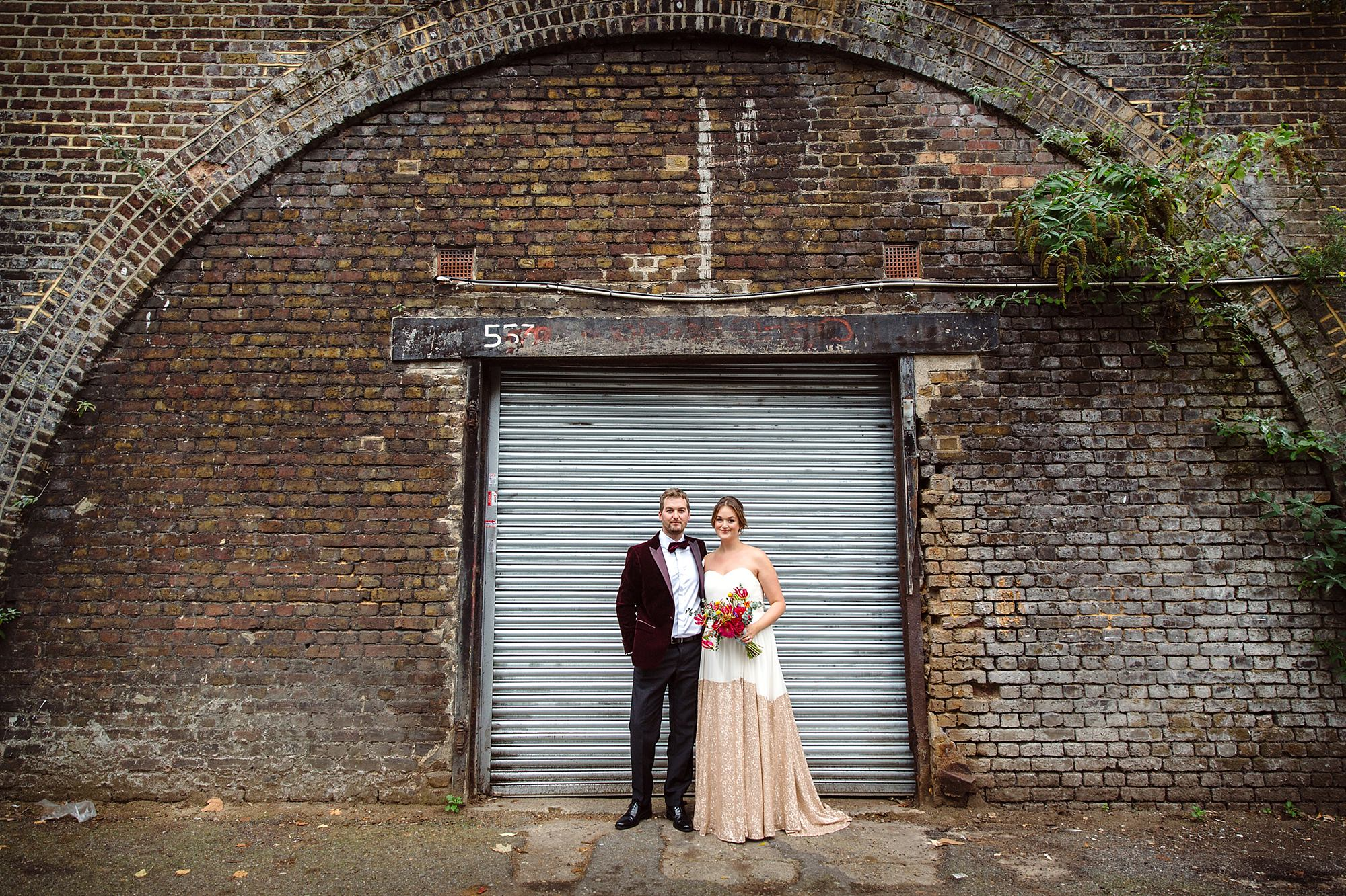 Fun London Wedding bride and groom standing in front of brixton railway arch