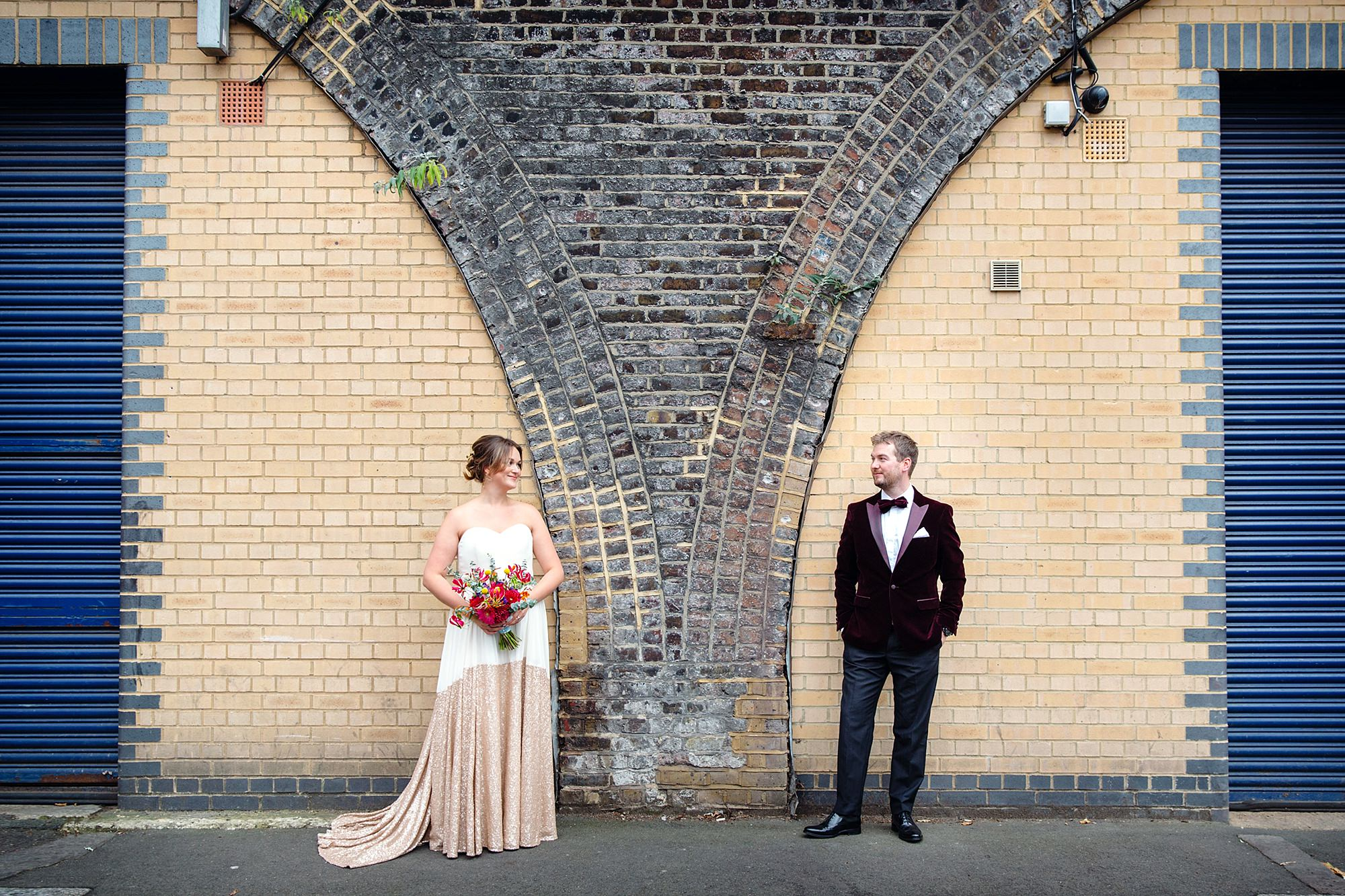 Fun London Wedding relaxed portrait of bride and groom in front of wall archway in brixton