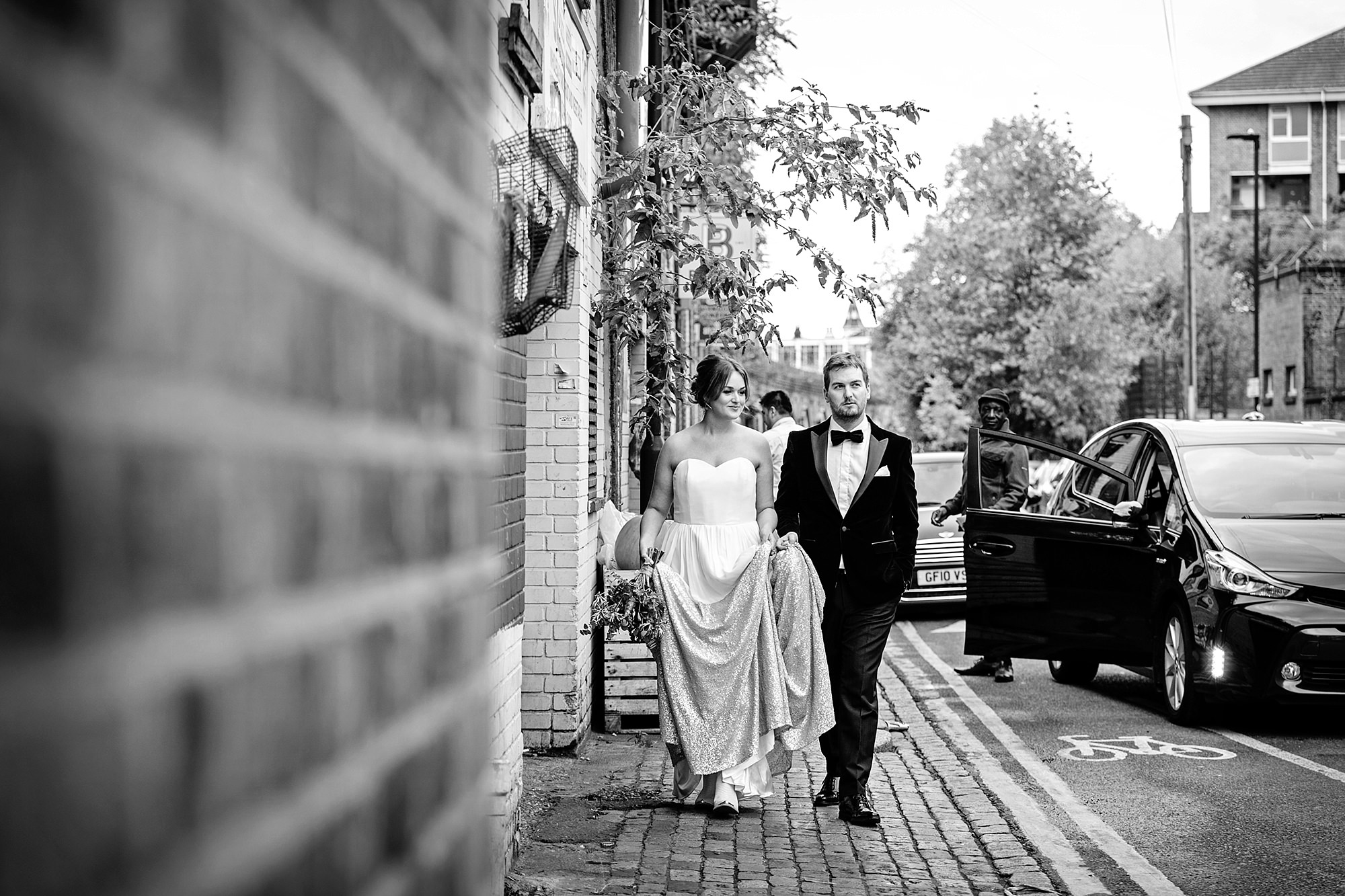 Fun London Wedding laid back portrait of bride and groom walking along the street in brixton