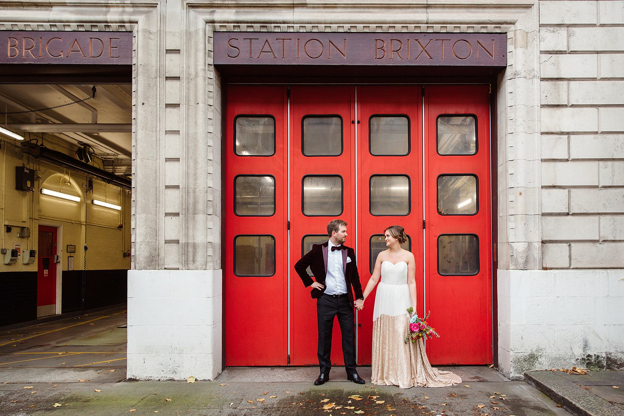 Fun London Wedding a bride and groom stand together in front of brixton fire station