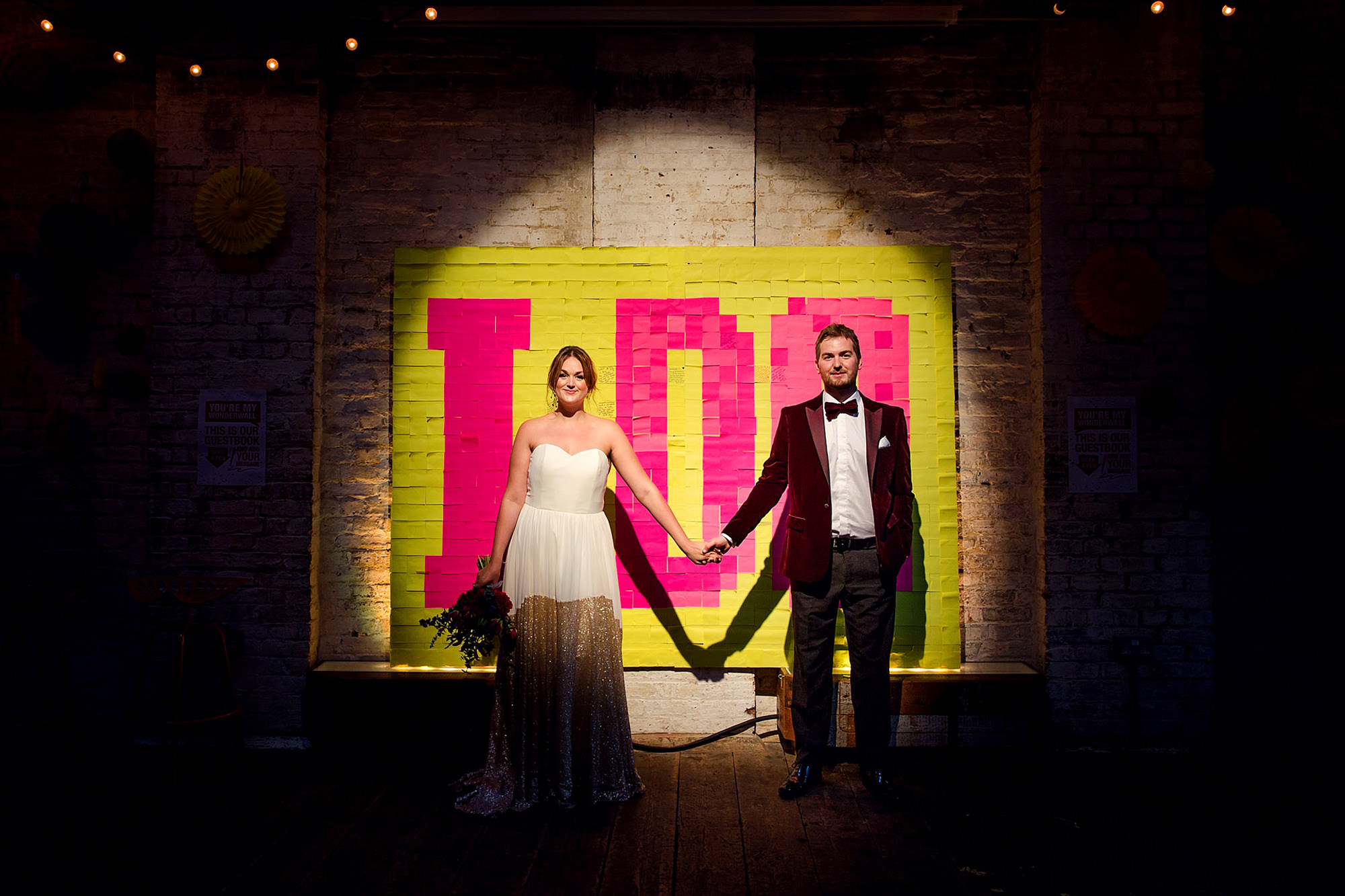Fun London Wedding portrait of bride and groom in front of giant post it note sign
