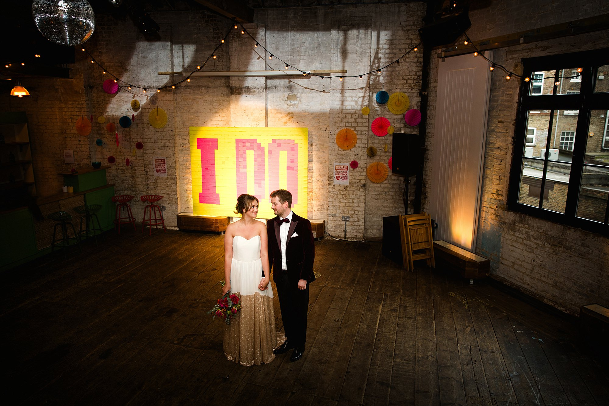Fun London Wedding bride and groom stand in front of a giant post it note sign
