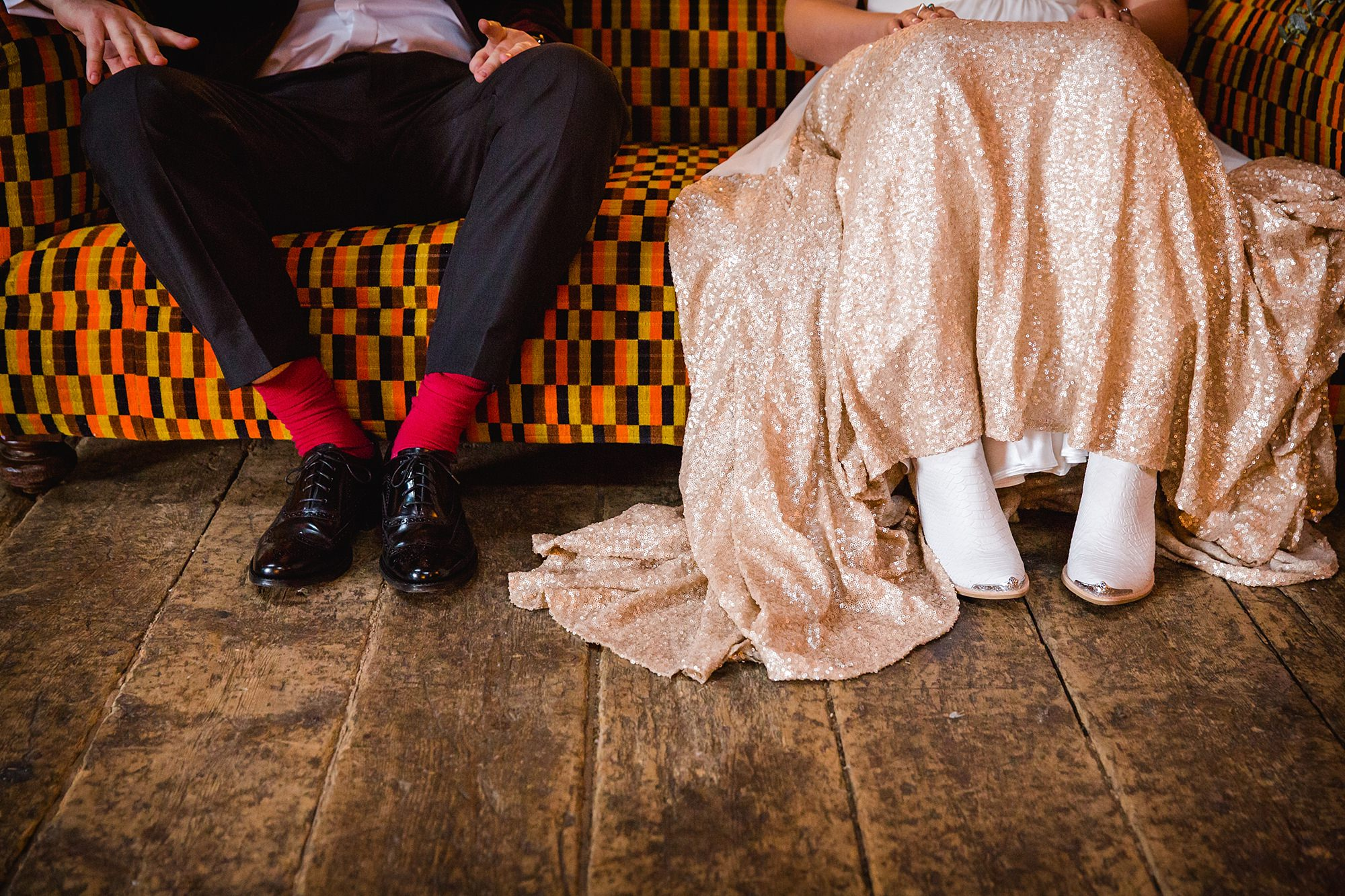 Fun London Wedding close up detail of bride's boots and groom's coloured socks sat in couch