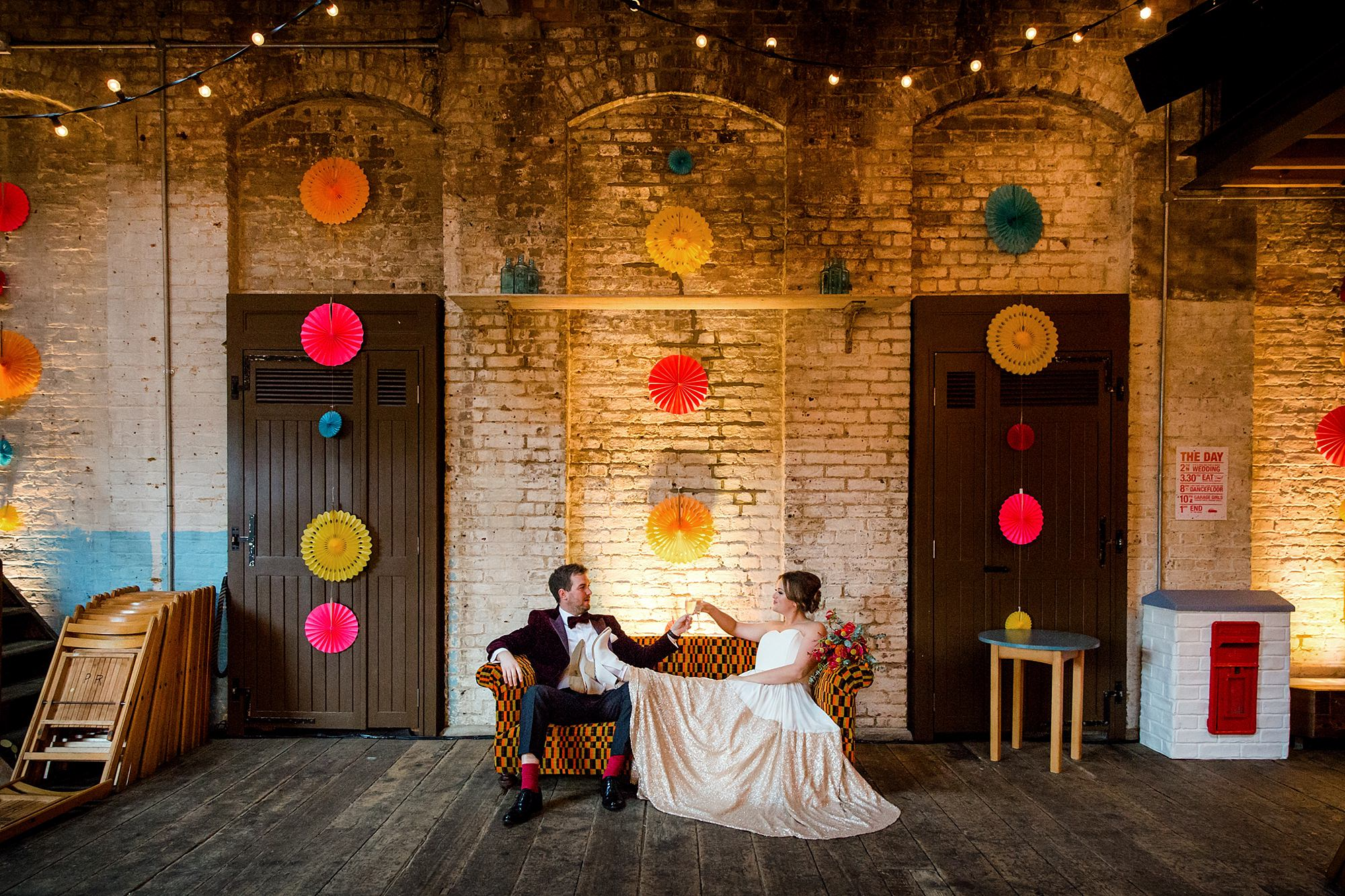 Fun London Wedding bride and groom sit together on couch at brixton east