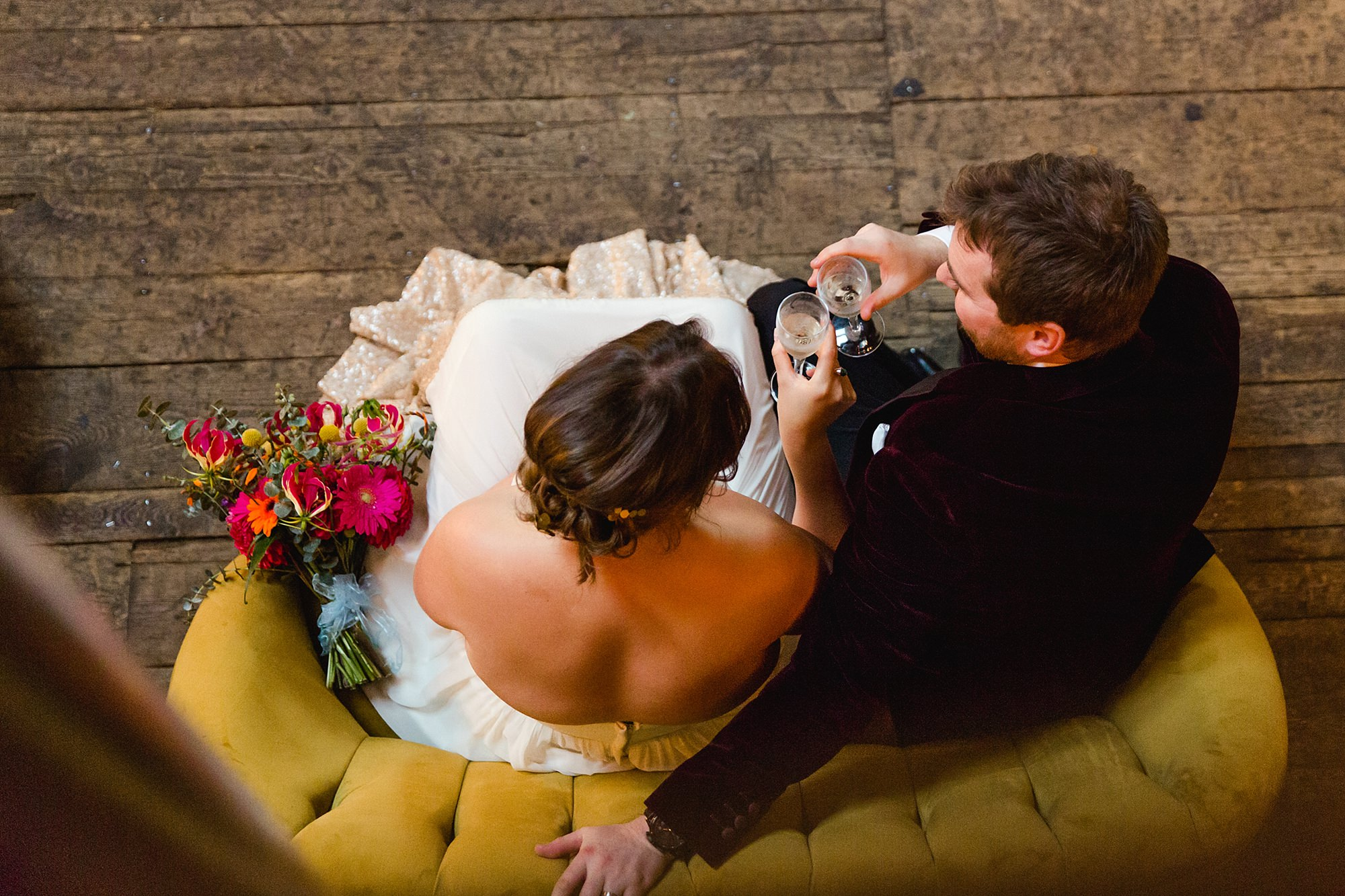 Fun London Wedding bride and groom toast each other whilst sat on sofa at brixton east