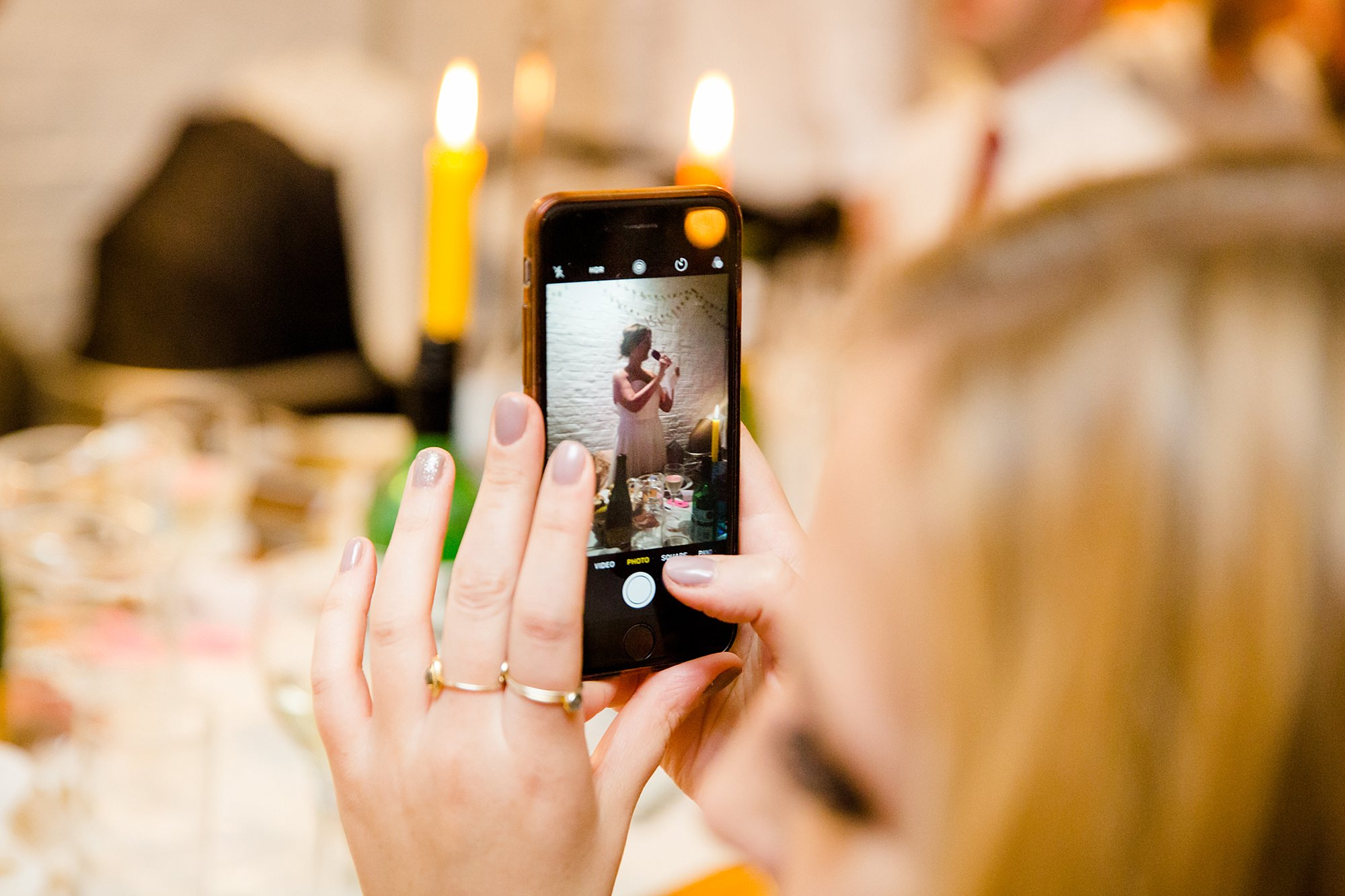 Fun London Wedding guest takes a picture of bride giving speech on her phone
