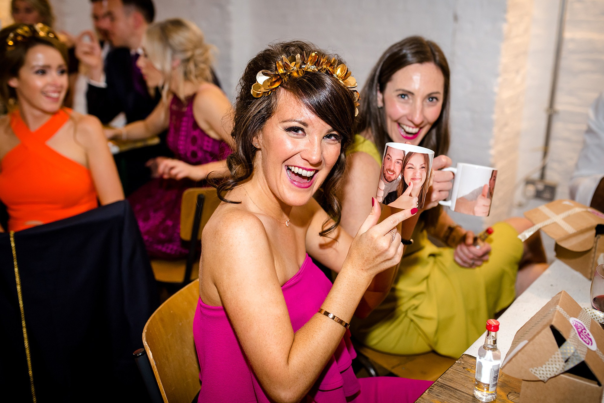Fun London Wedding bridesmaid shows off a mug with bride and rooms faces on as quiz prize
