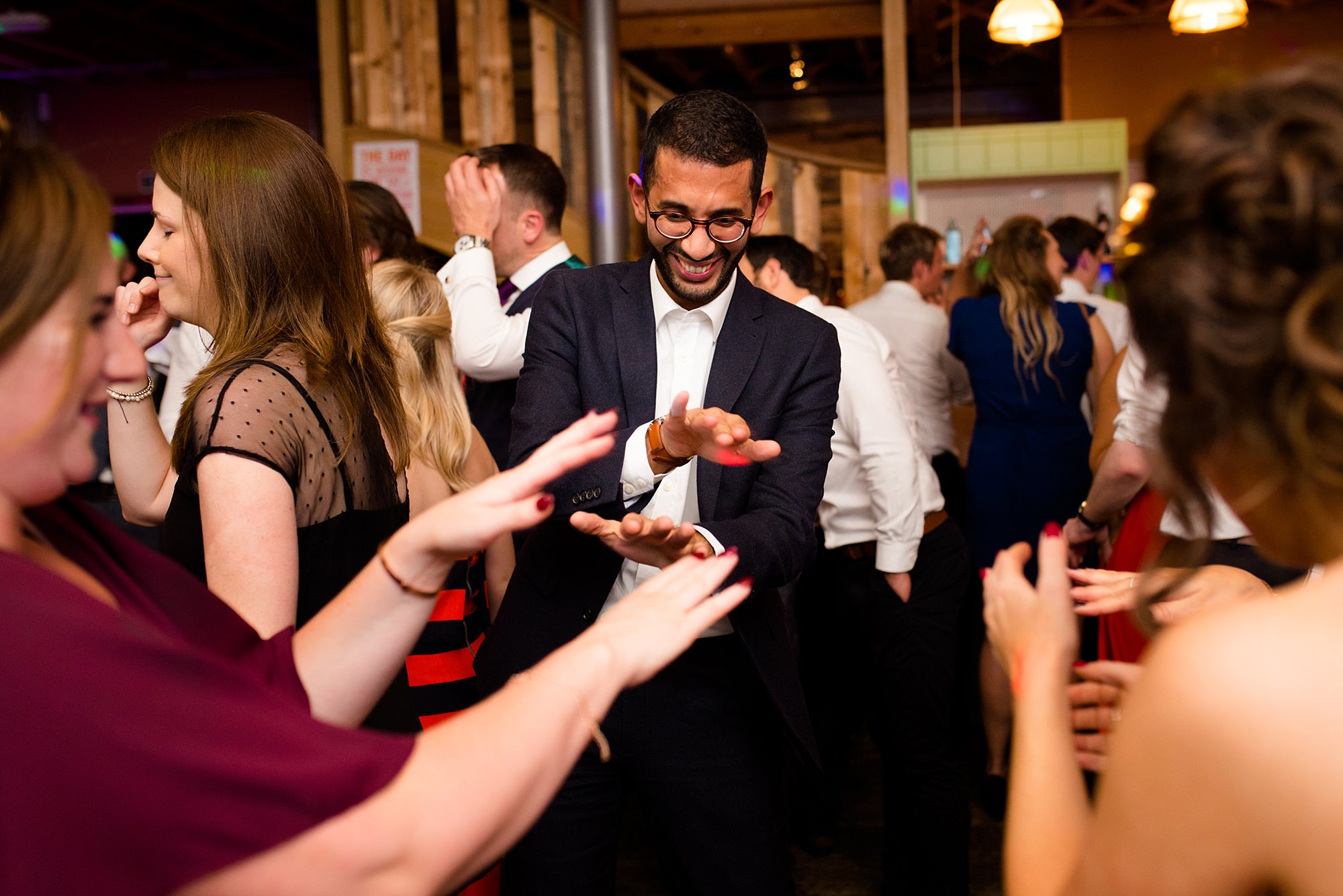 Fun London Wedding guests laugh as they dance together at brixton east wedding