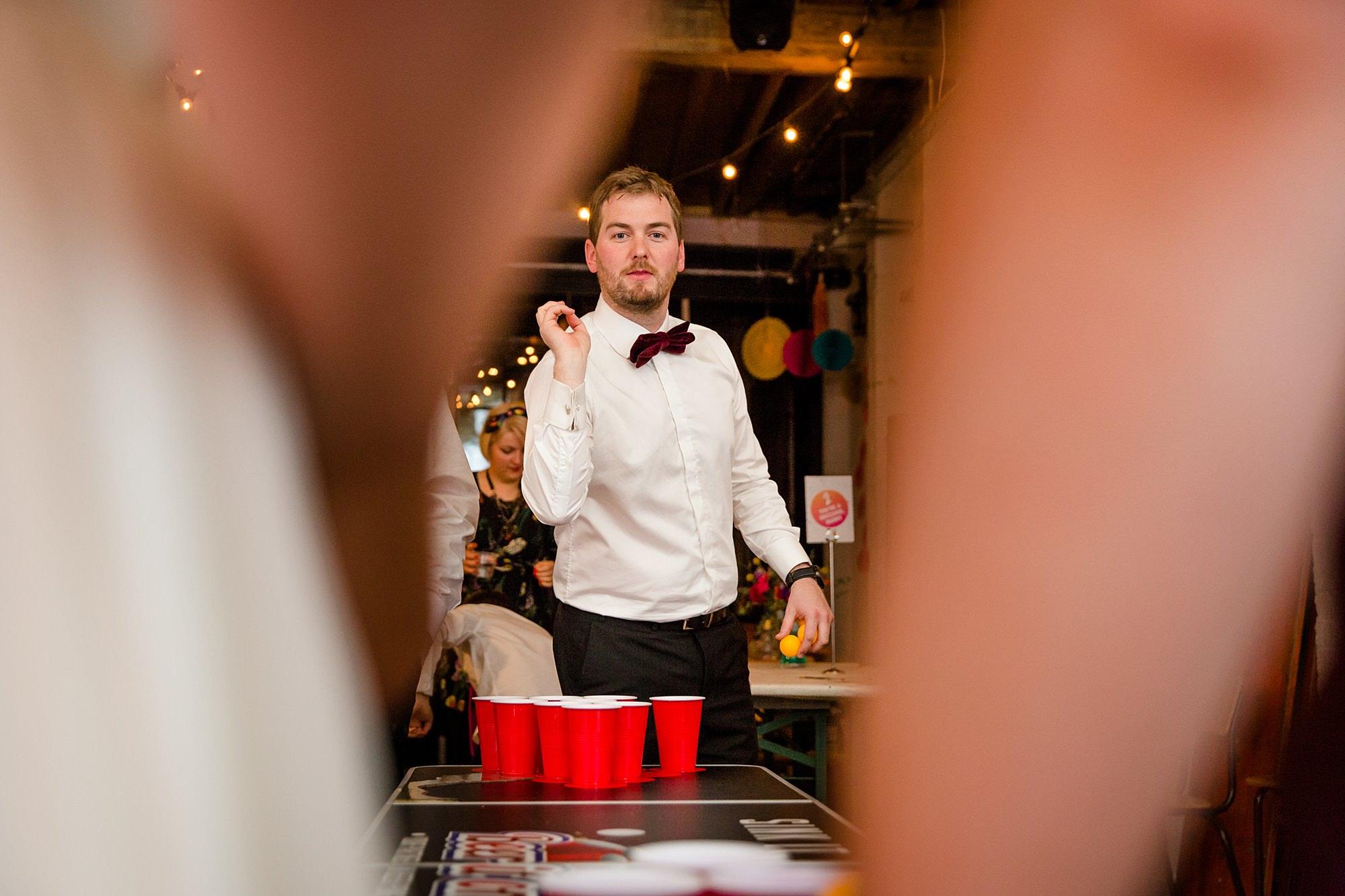 Fun London Wedding groom playing beer pong
