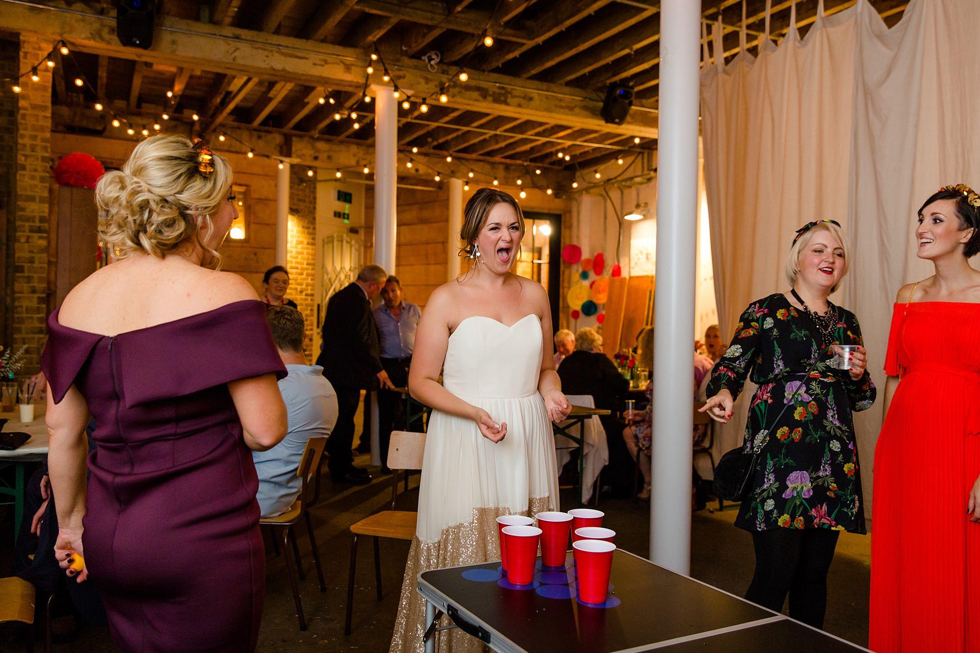 Fun London Wedding bride playing beer pong