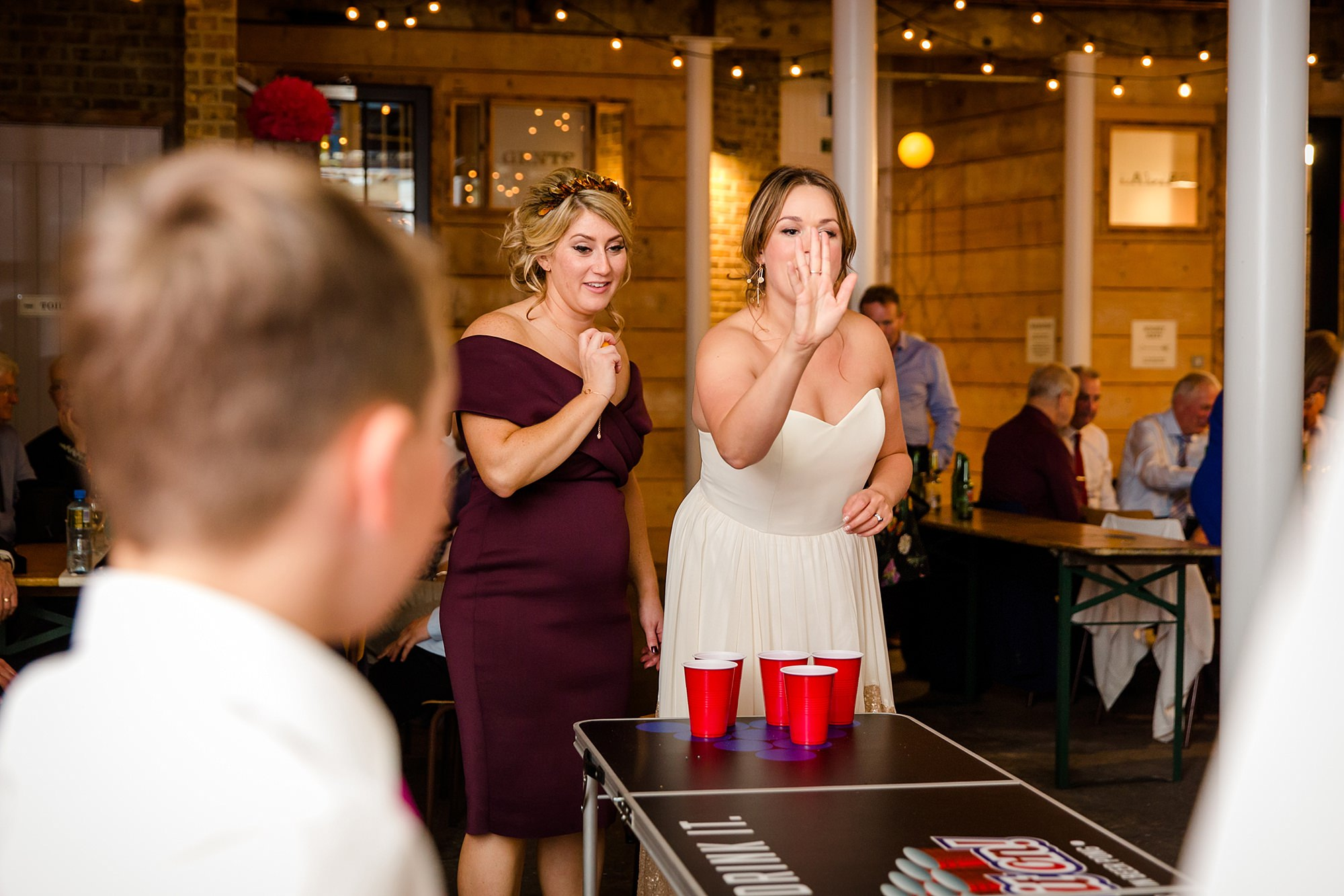 Fun London Wedding bride throwing beer pong ball