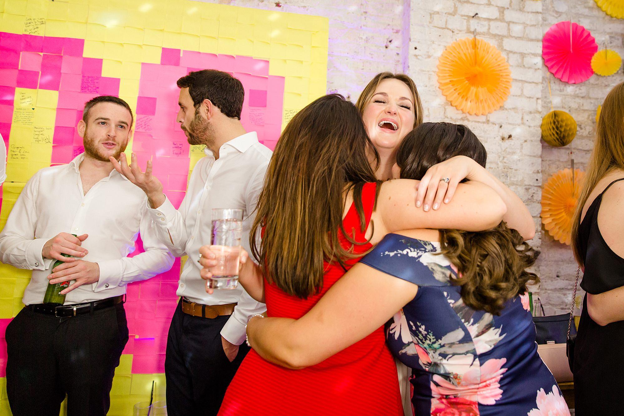 Fun London Wedding bride hugs guests while dancing at brixton wedding
