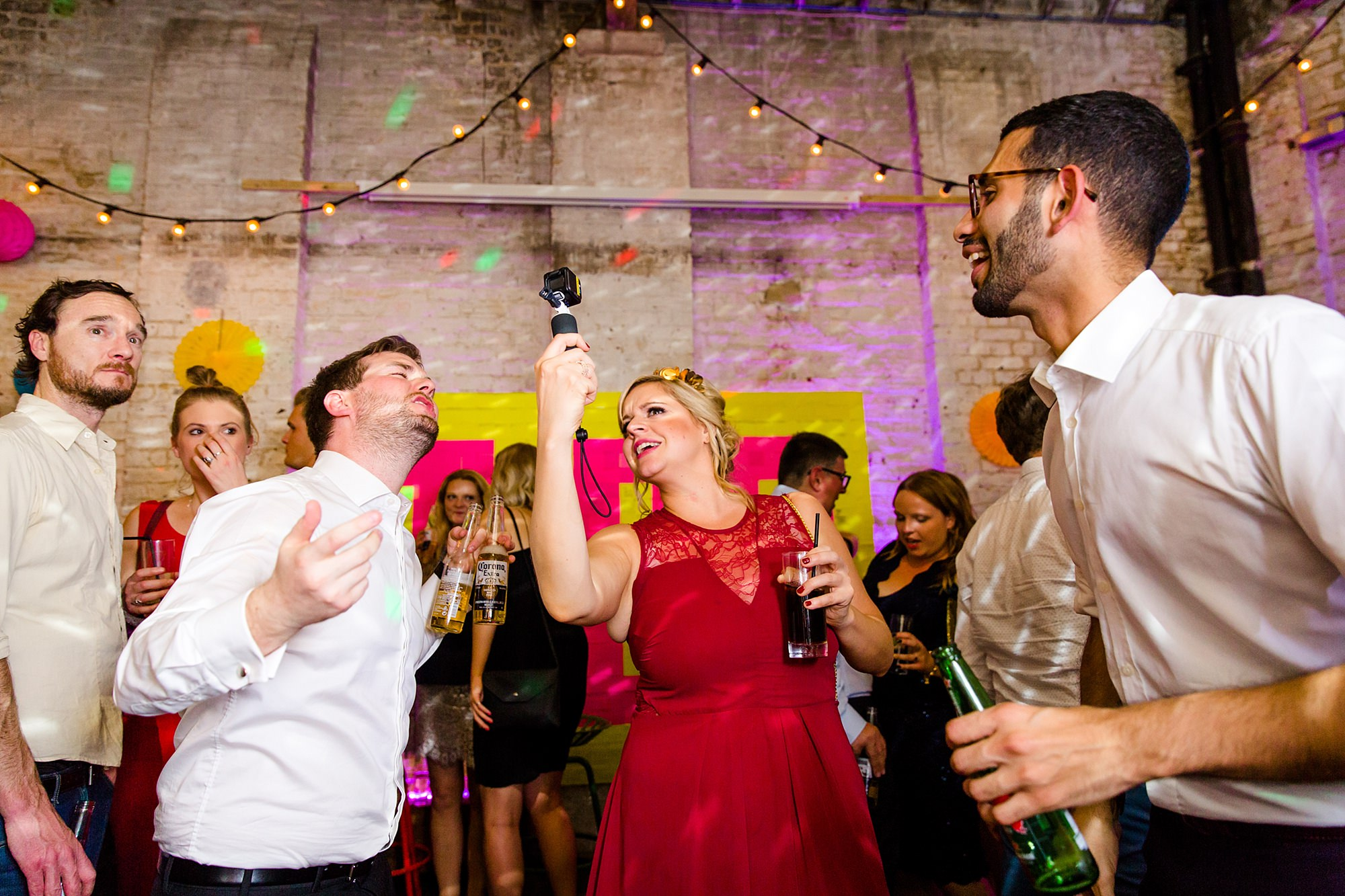 Fun London Wedding guests sing at a go pro camera during wedding party
