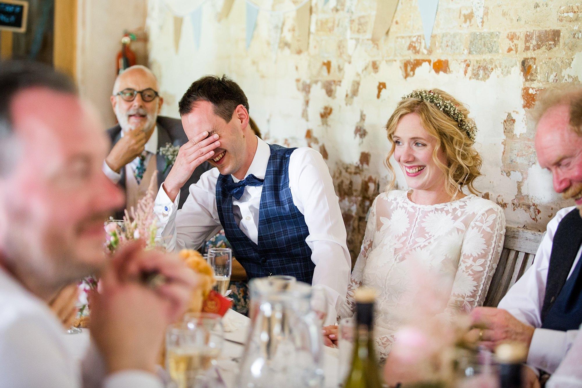 Isis Farmhouse Oxford Wedding fun portrait of groom cringing during best man speech