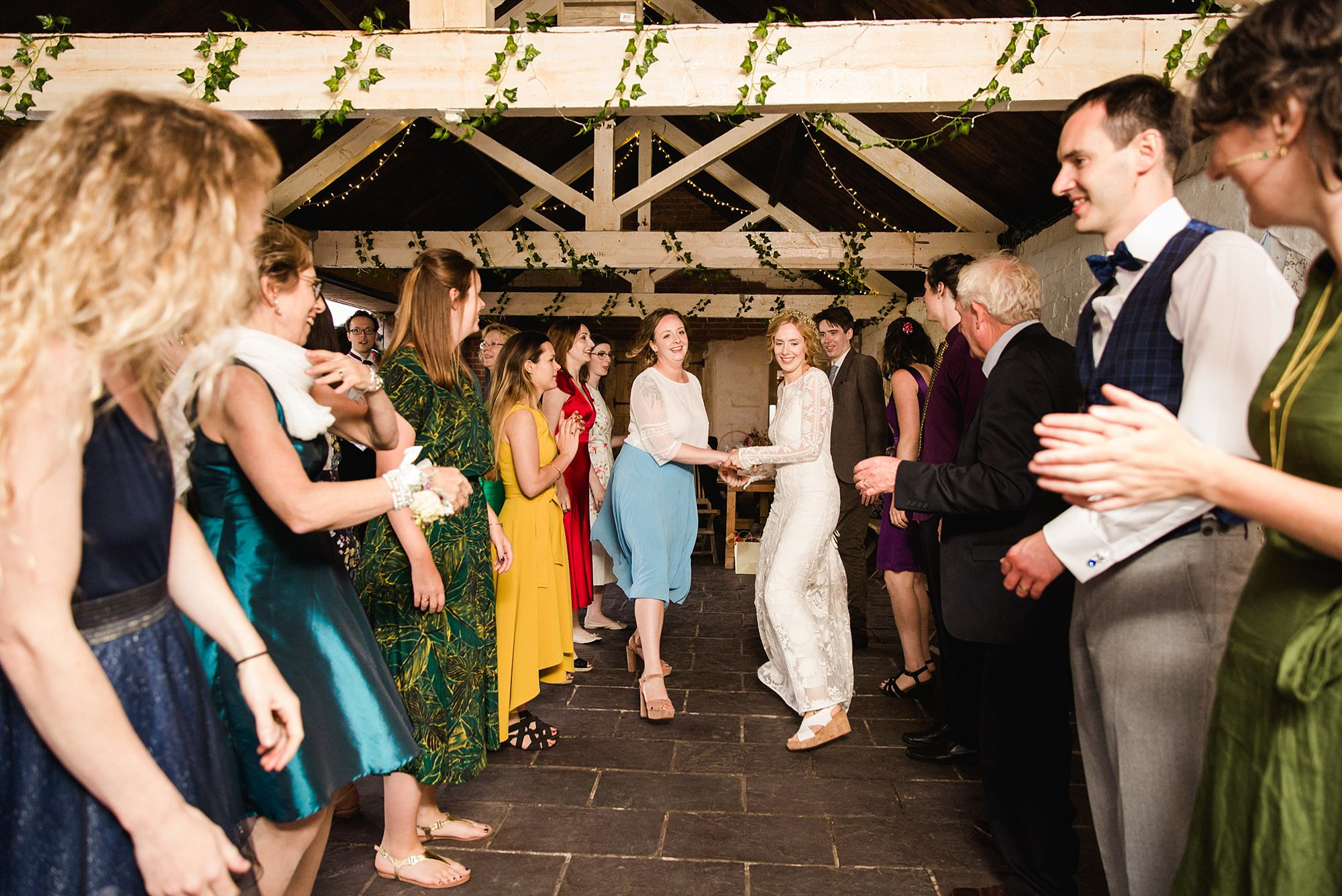Isis Farmhouse Oxford Wedding bride dances with bridesmaid in ceilidh