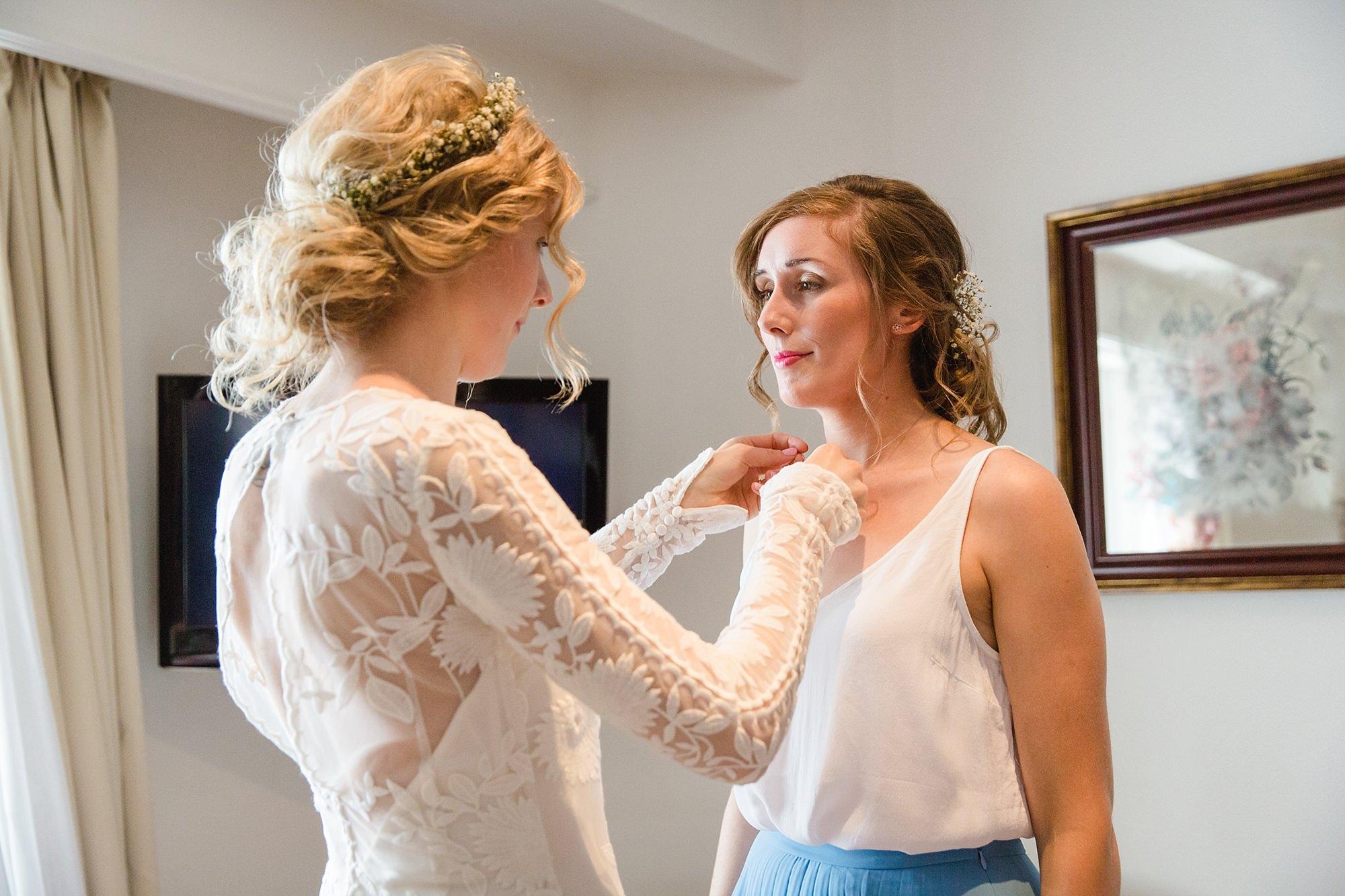 Isis Farmhouse Oxford Wedding bride helps bridesmaid with her necklace