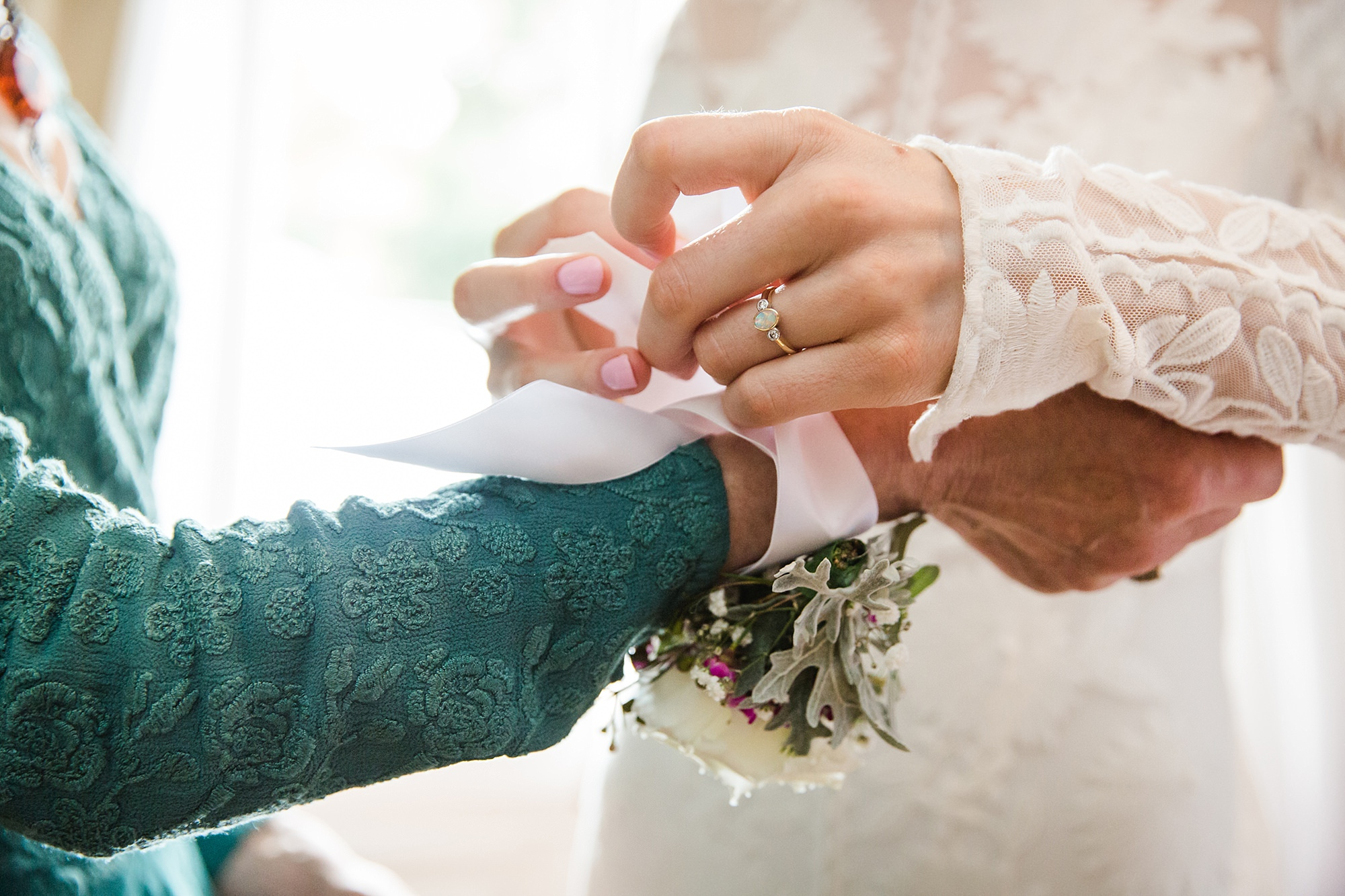 Isis Farmhouse Oxford Wedding close up detail of bride typging mother of bride's corsage