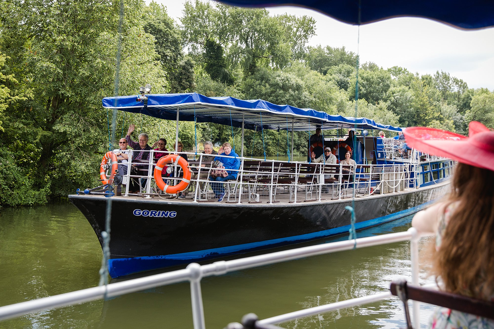 Isis Farmhouse Oxford Wedding guests wave to passing boat