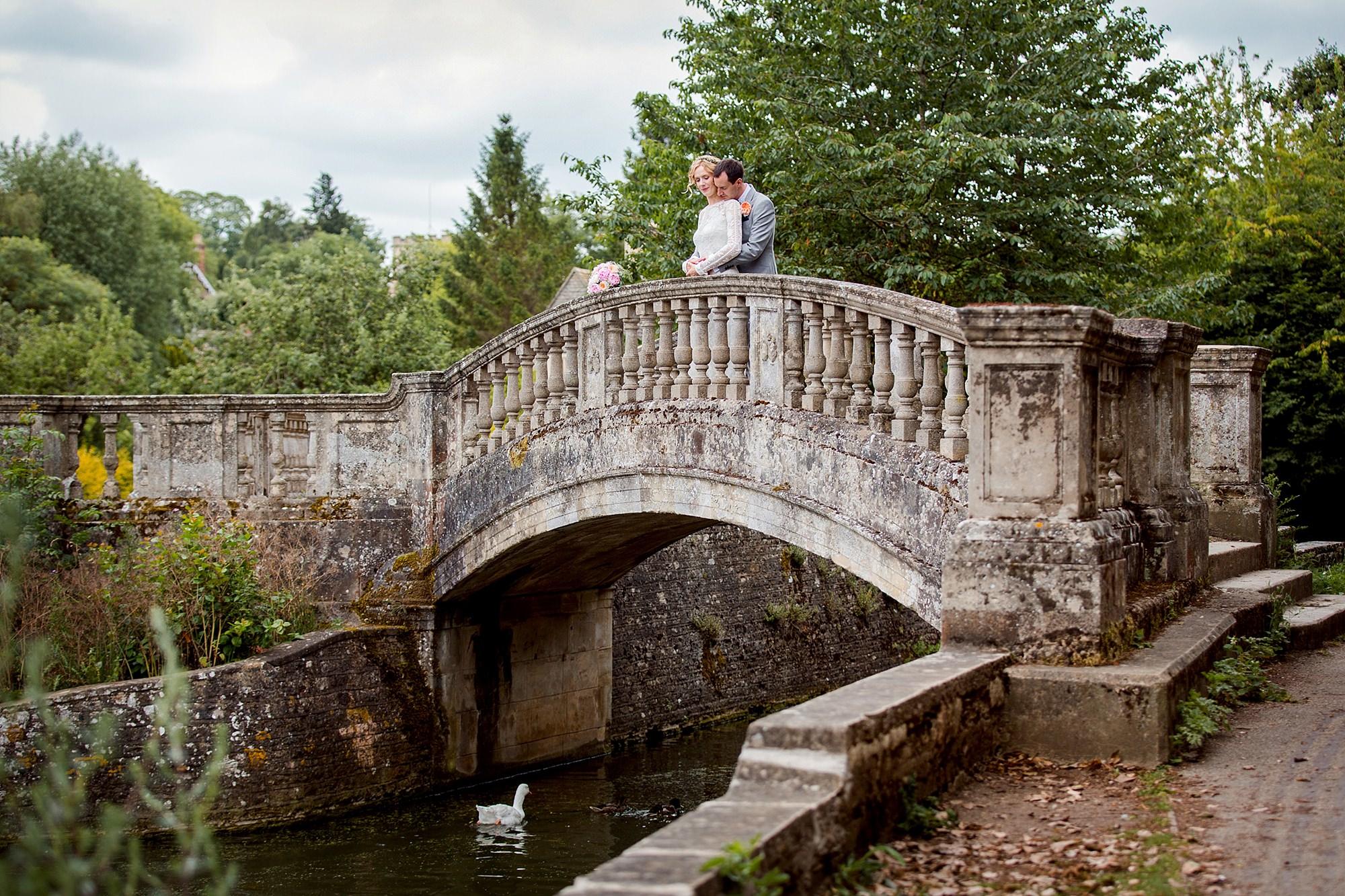 Isis Farmhouse Oxford Wedding portrait of bride and room hugging on bridge